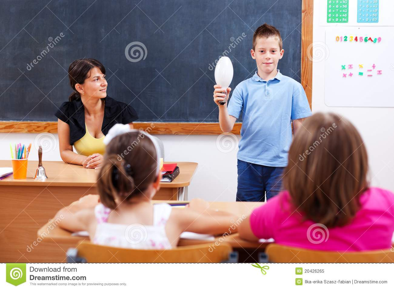 Schoolboy holding bulb in front of class