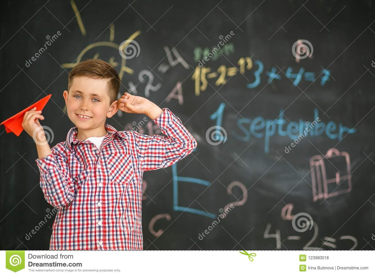 A schoolboy holding a red airplane in the hands of a training board