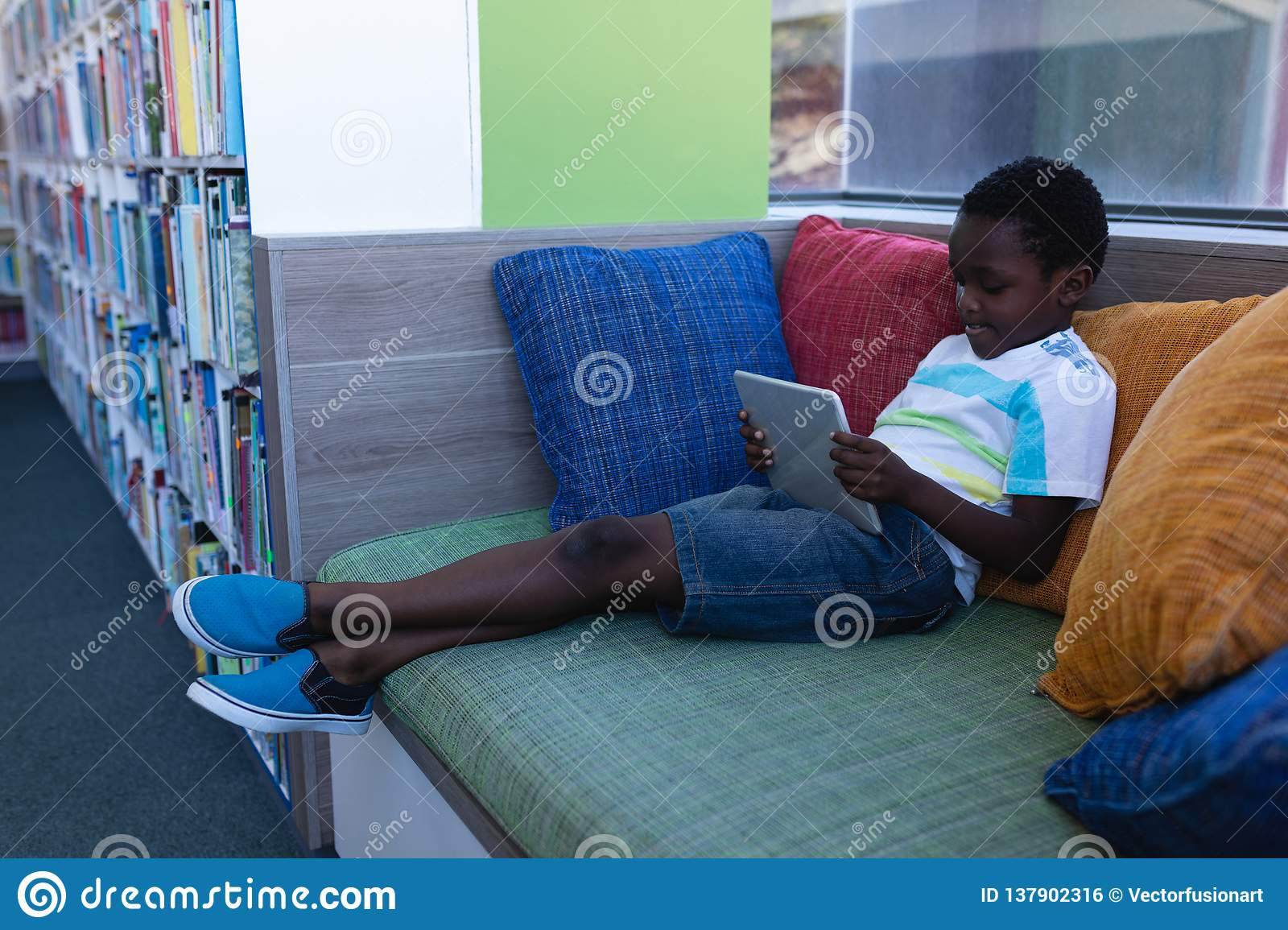 Schoolboy playing on digital tablet while sitting on couch in school library