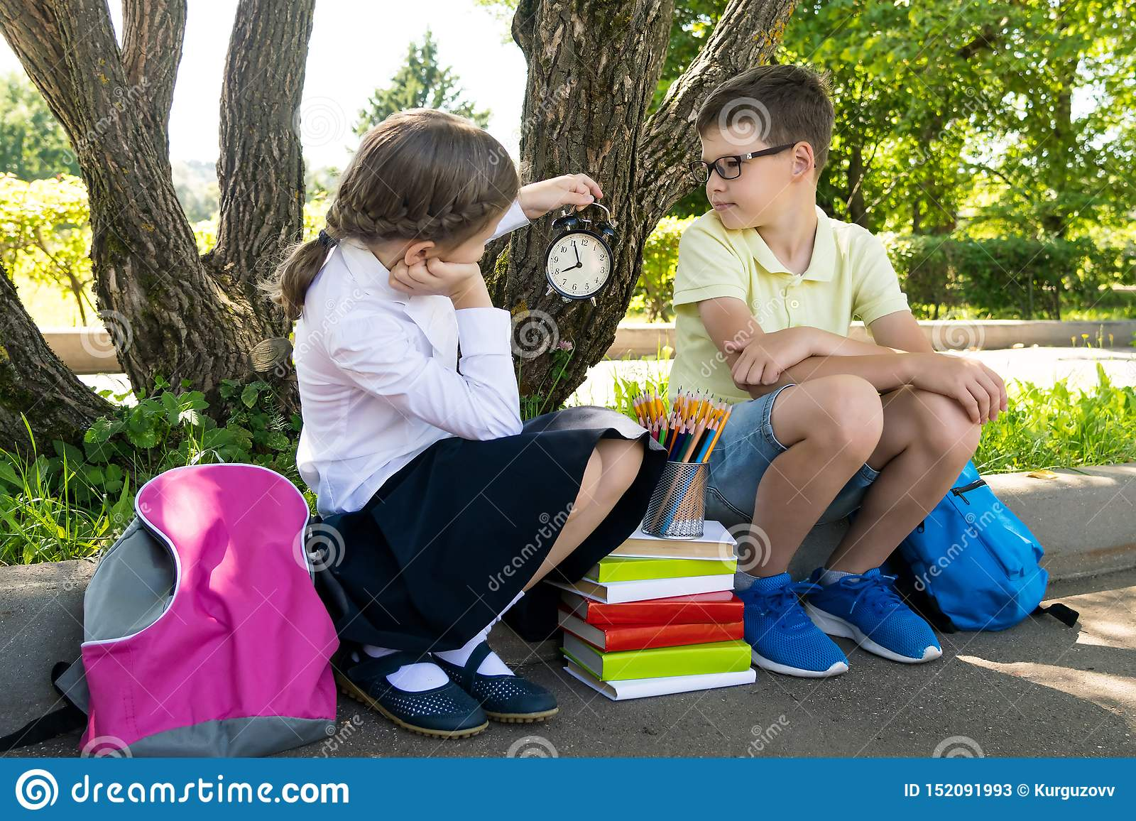 Schoolboy and schoolgirl look at the clock and wait for the lesson to begin in the park