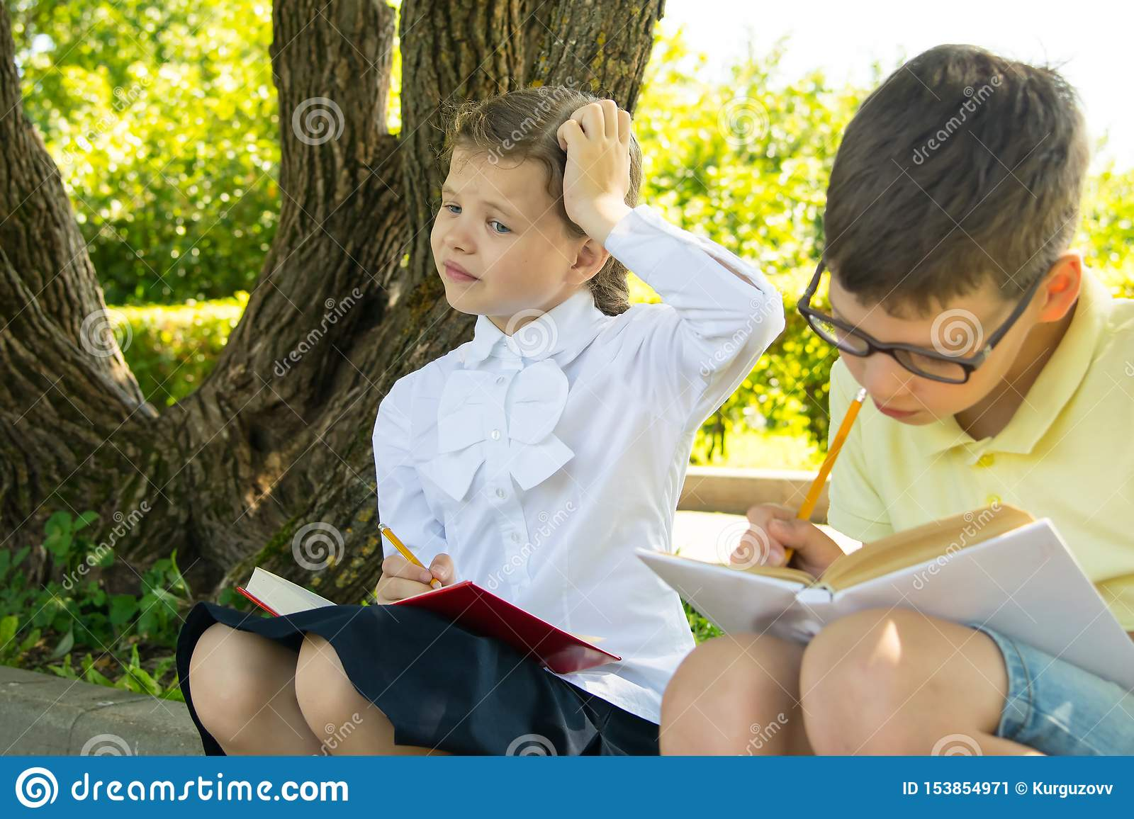 Schoolchildren doing homework, in the park in the fresh air, the girl thought about the task and scratches her head