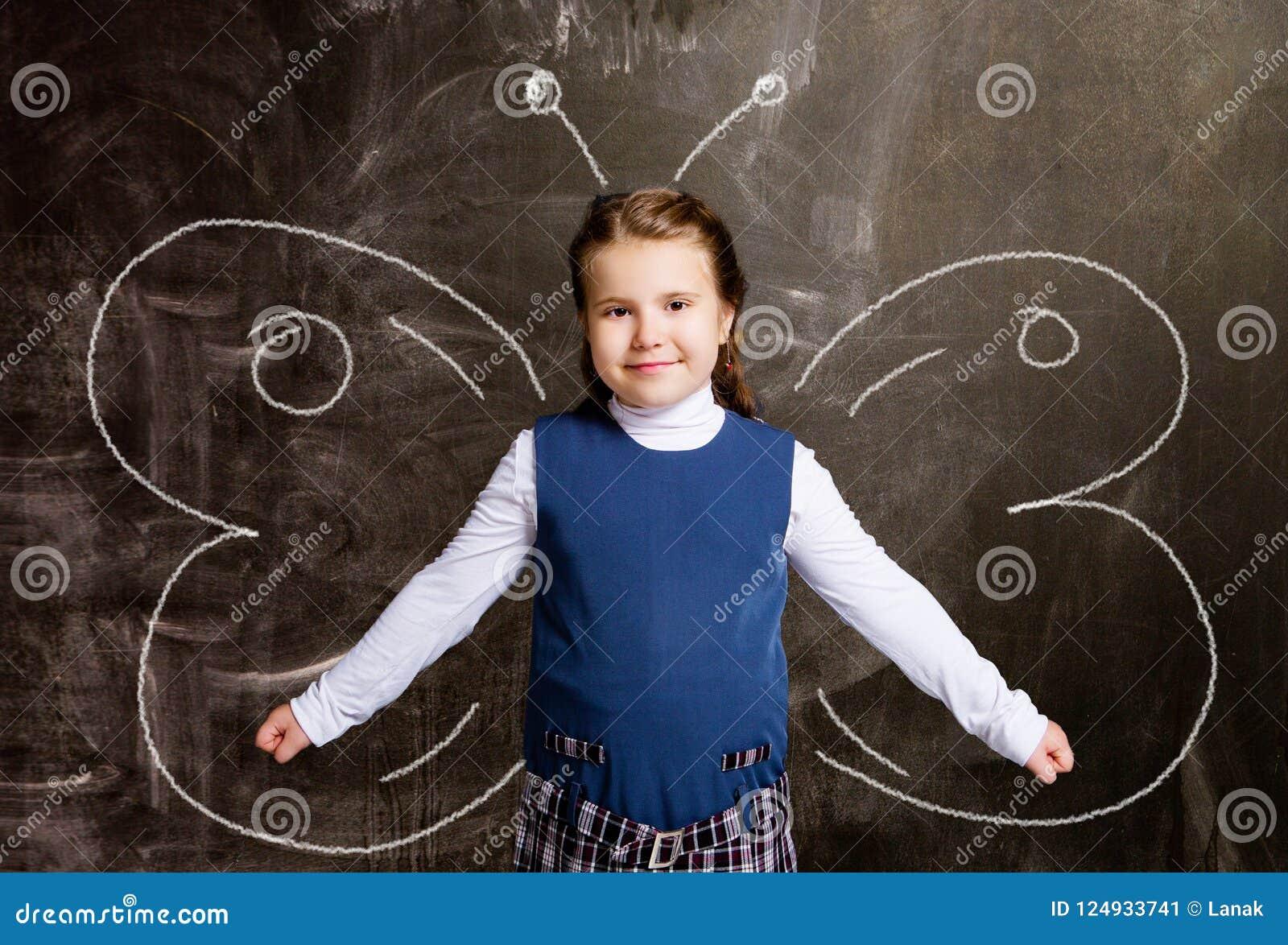 Schoolgirl against chalkboard, with butterfly wings