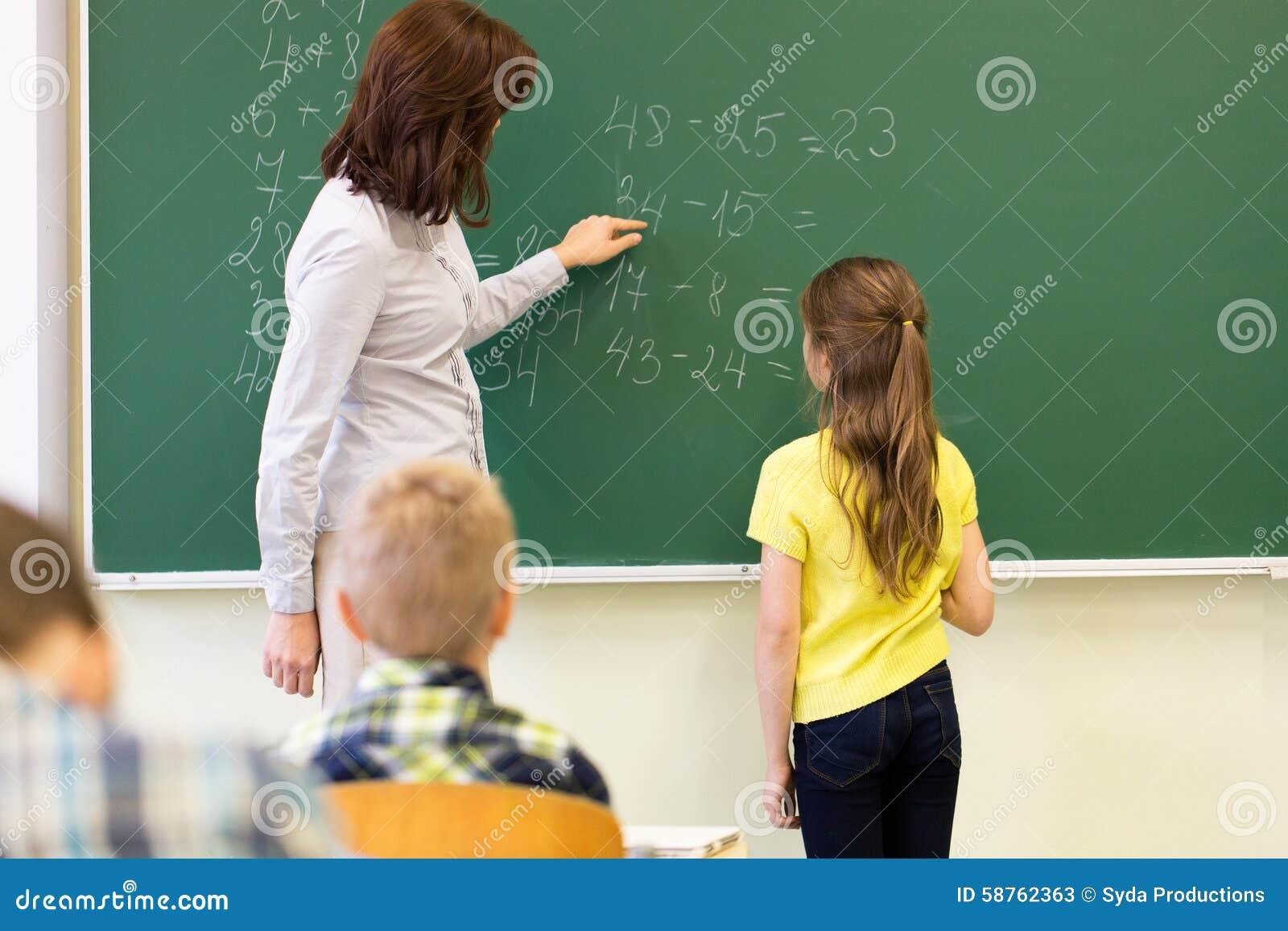 Schoolgirl And Teacher With Task On Chalk Board