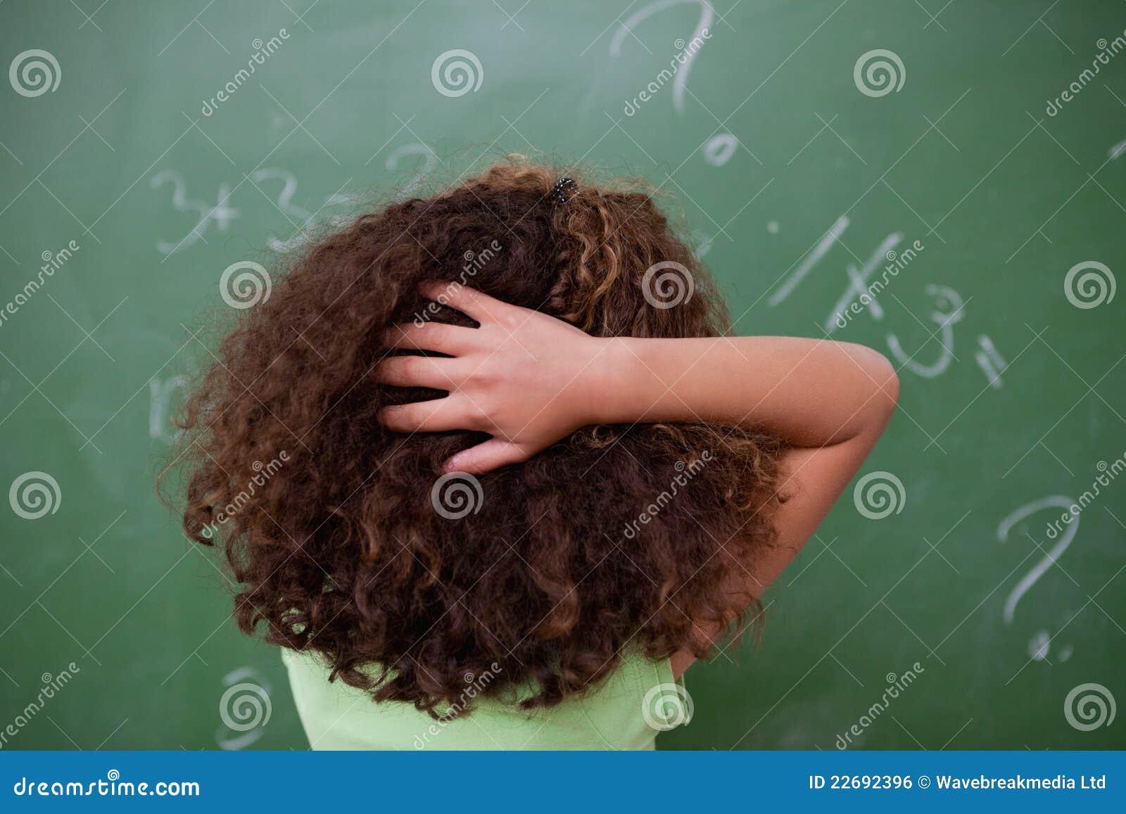 Schoolgirlen som är tänkande om algebra, fördriver skrapa baksidaen av H