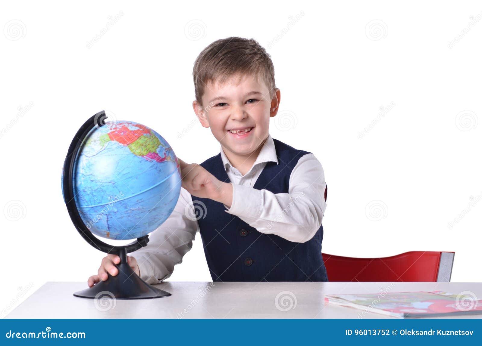Schooljongen bij de bureaulach en het richten op een bol