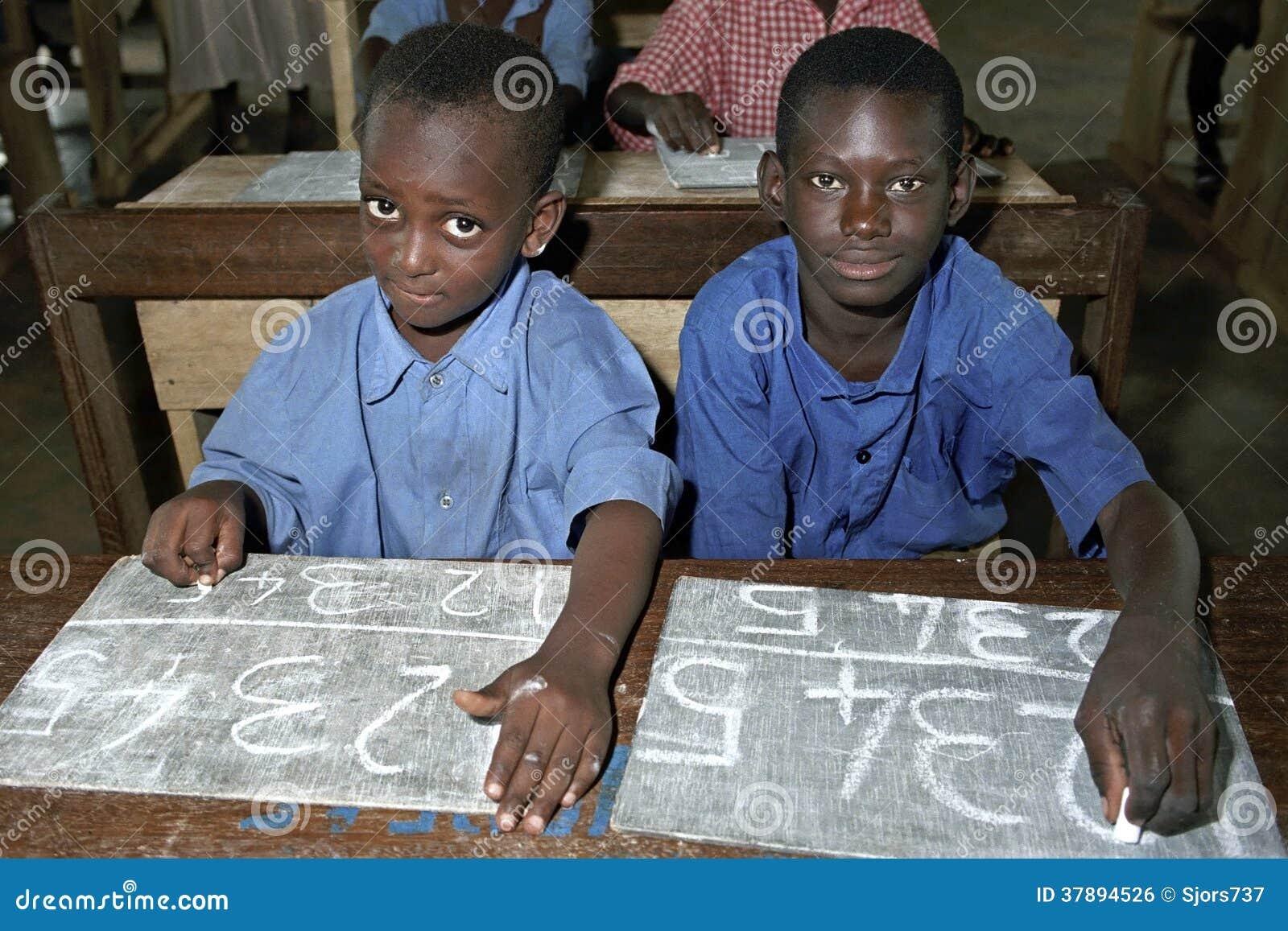Schoolkinderen die met krijt op een lei schrijven