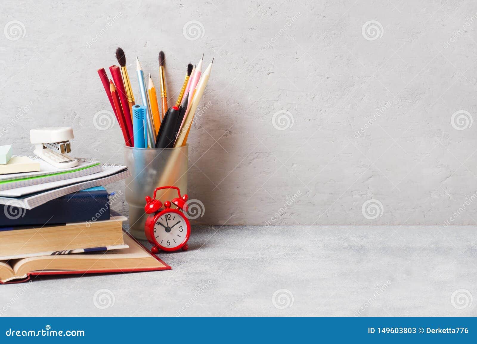 Schoollevering, de potloden van boekennotitieboekjes op grijze achtergrond met exemplaarruimte