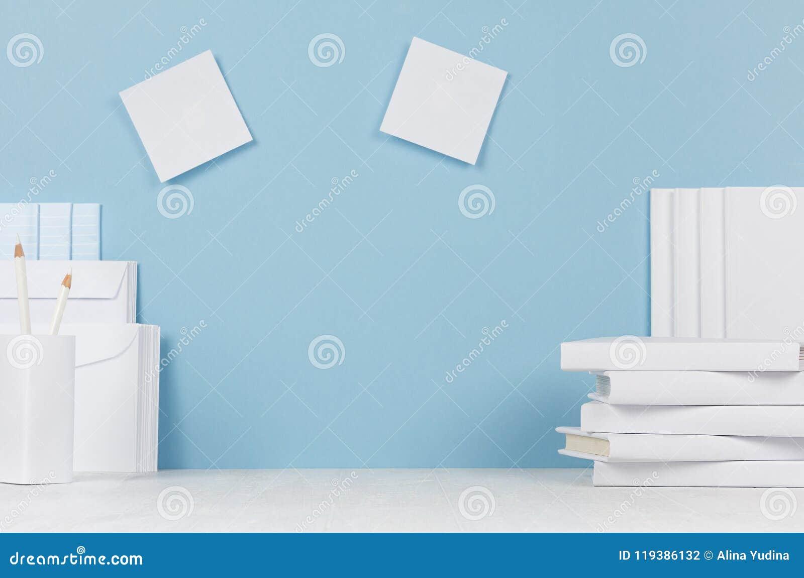 Schoolmalplaatje - witte boeken, kantoorbehoeften, lege stickers op wit bureau en zachte blauwe achtergrond