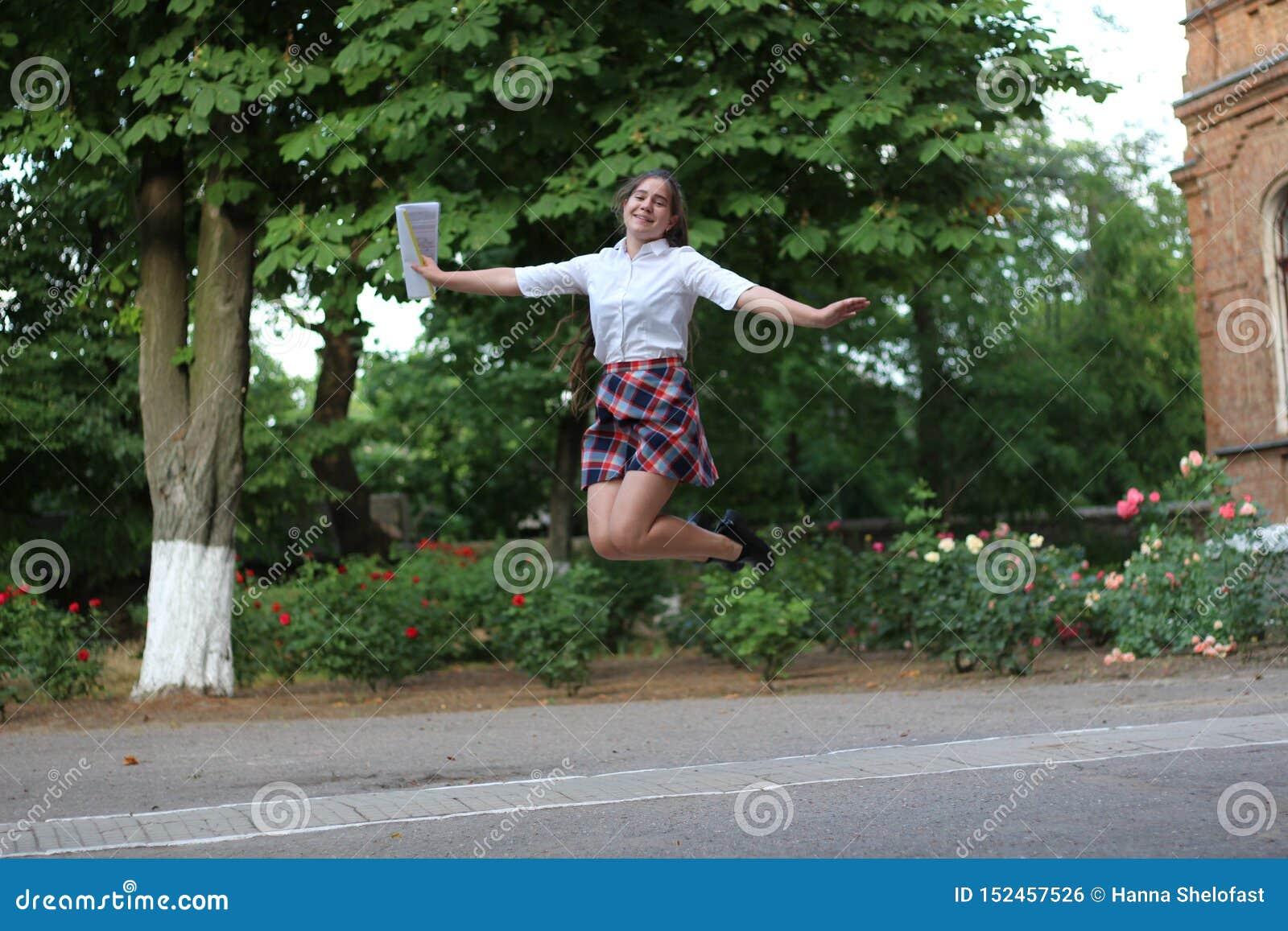 Schoolmeisje die voor vreugde springen