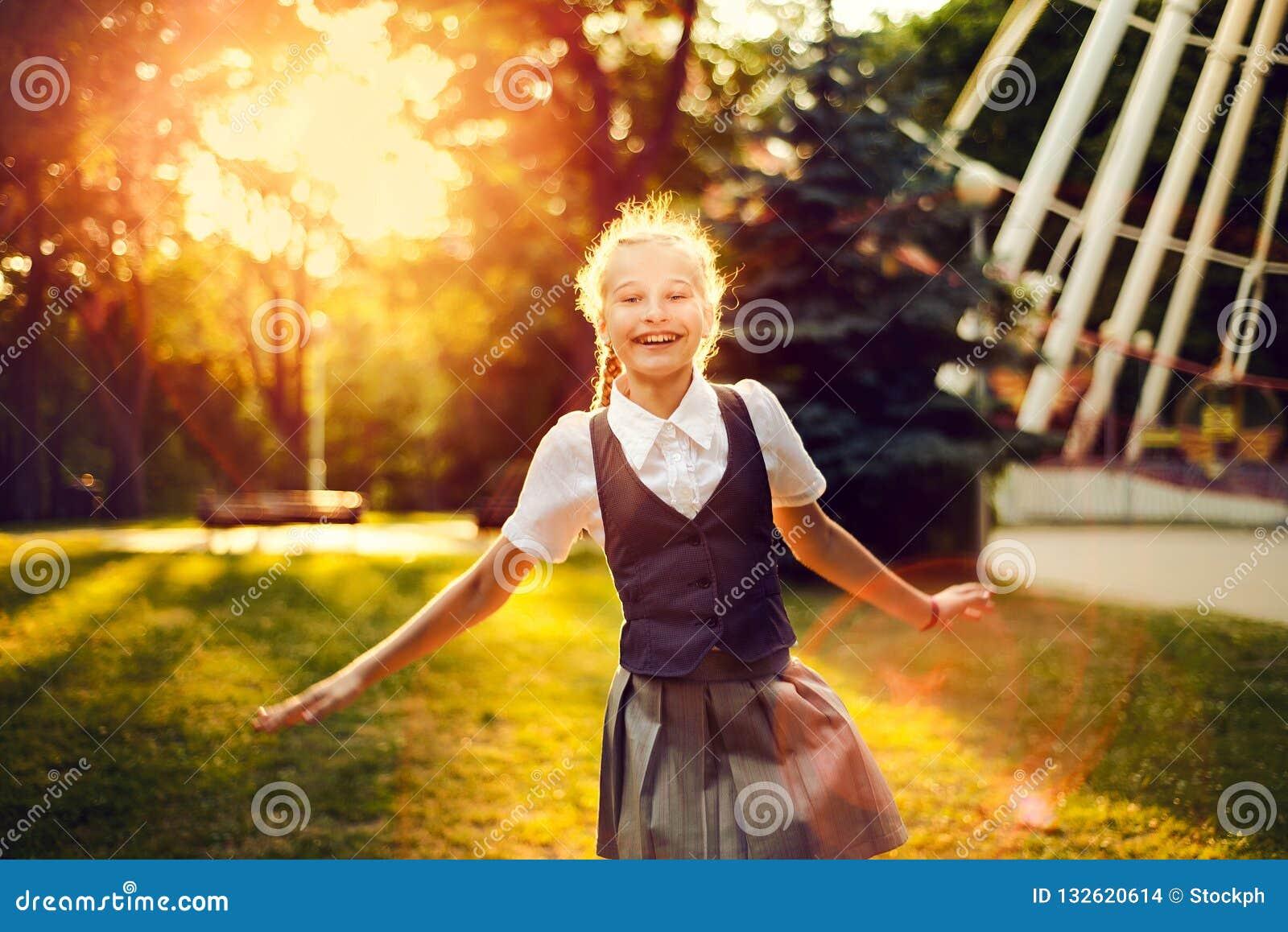 Schoolmeisje in eenvormig met vlechten het blije dansen bij zonsondergang i