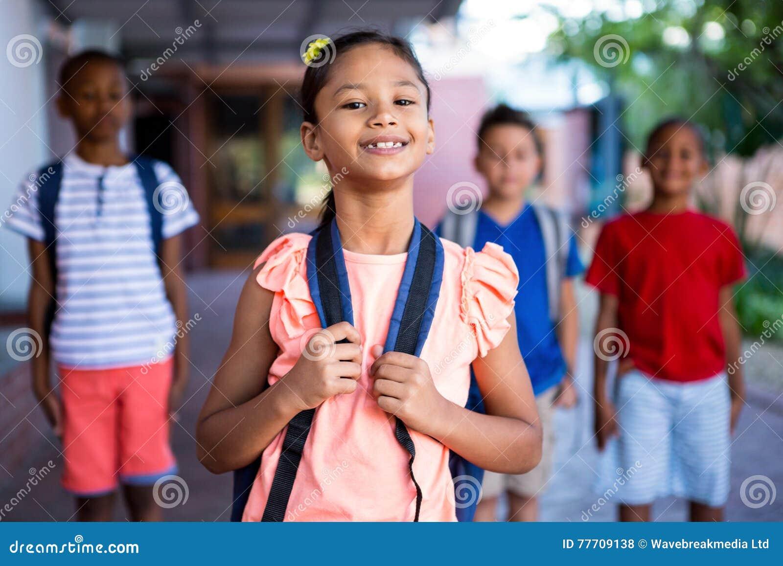 Schoolmeisje met klasgenoten bij schoolgang