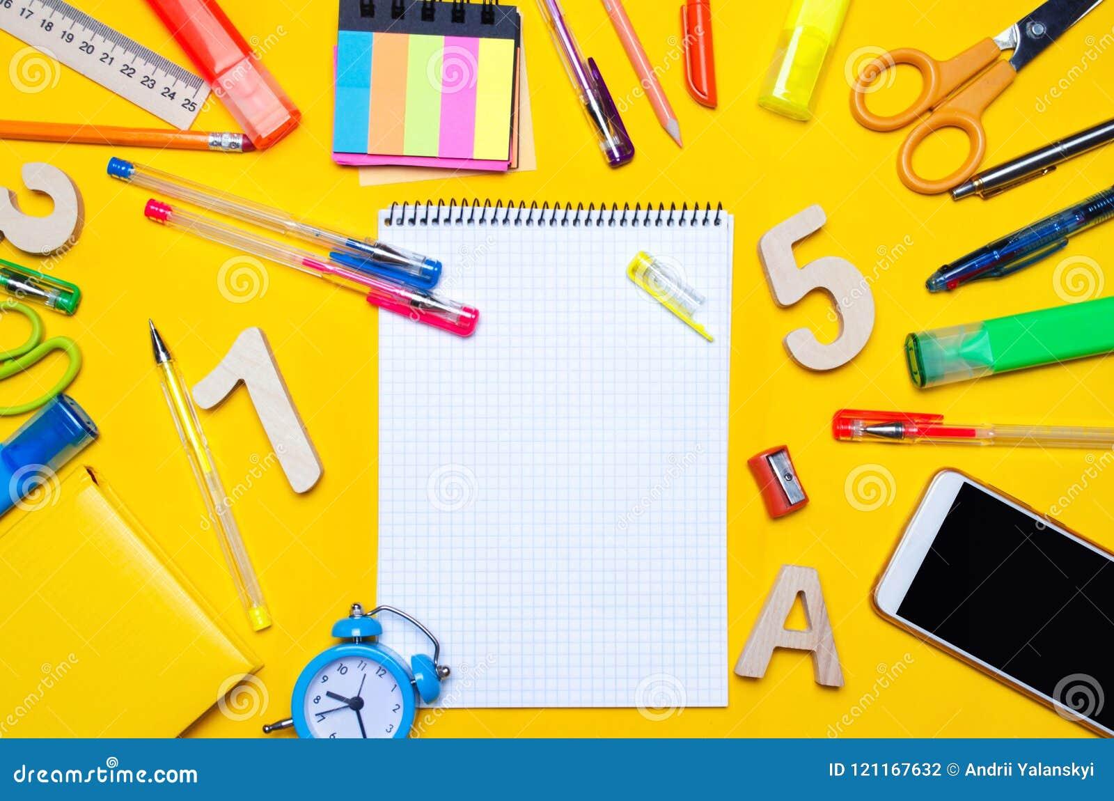 Schooltoebehoren op een bureau op een gele achtergrond Concept onderwijs kantoorbehoeften horloges, gekleurde pennen, telefoon, t
