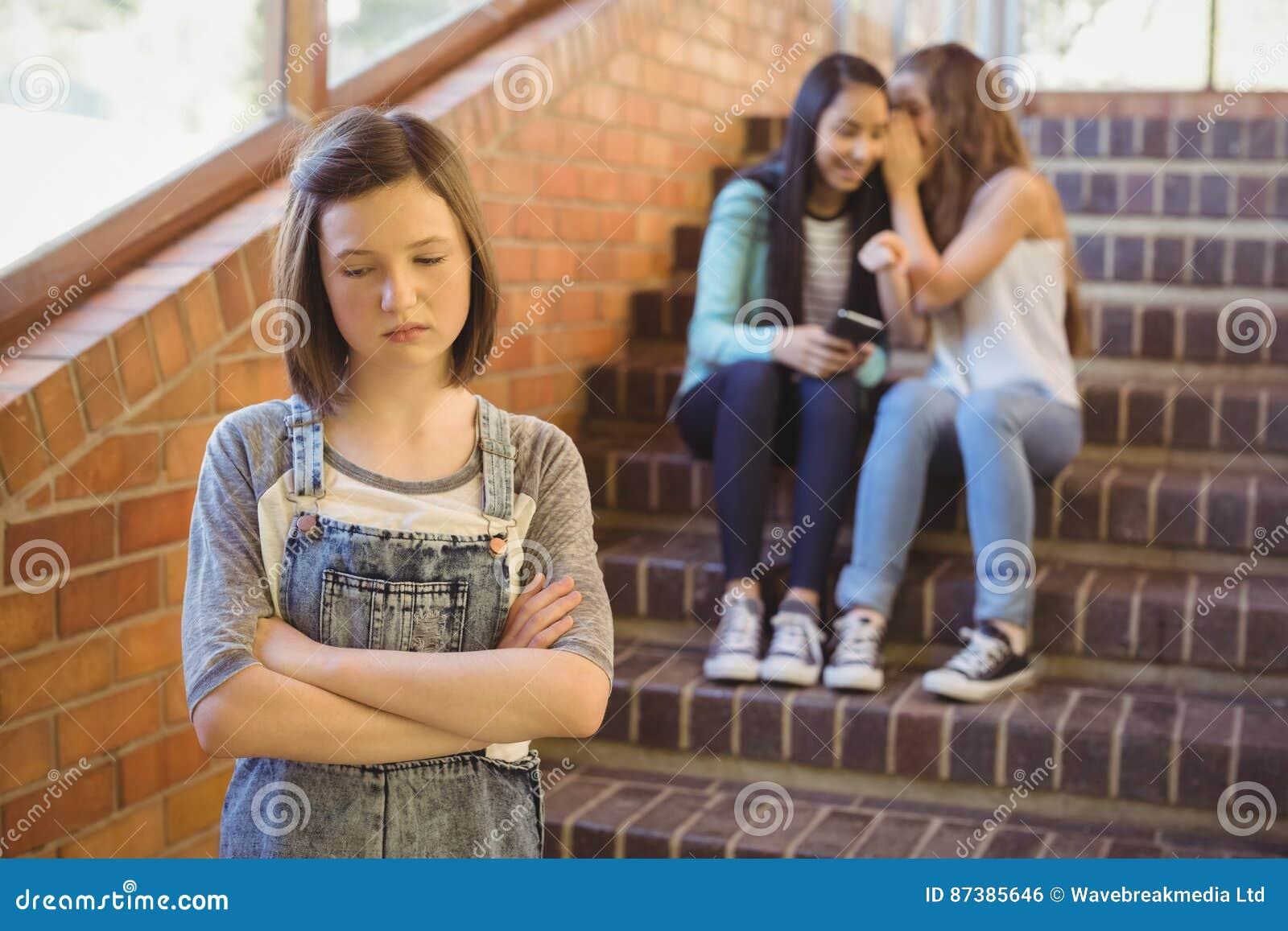 Schoolvrienden die een droevig meisje in schoolgang intimideren