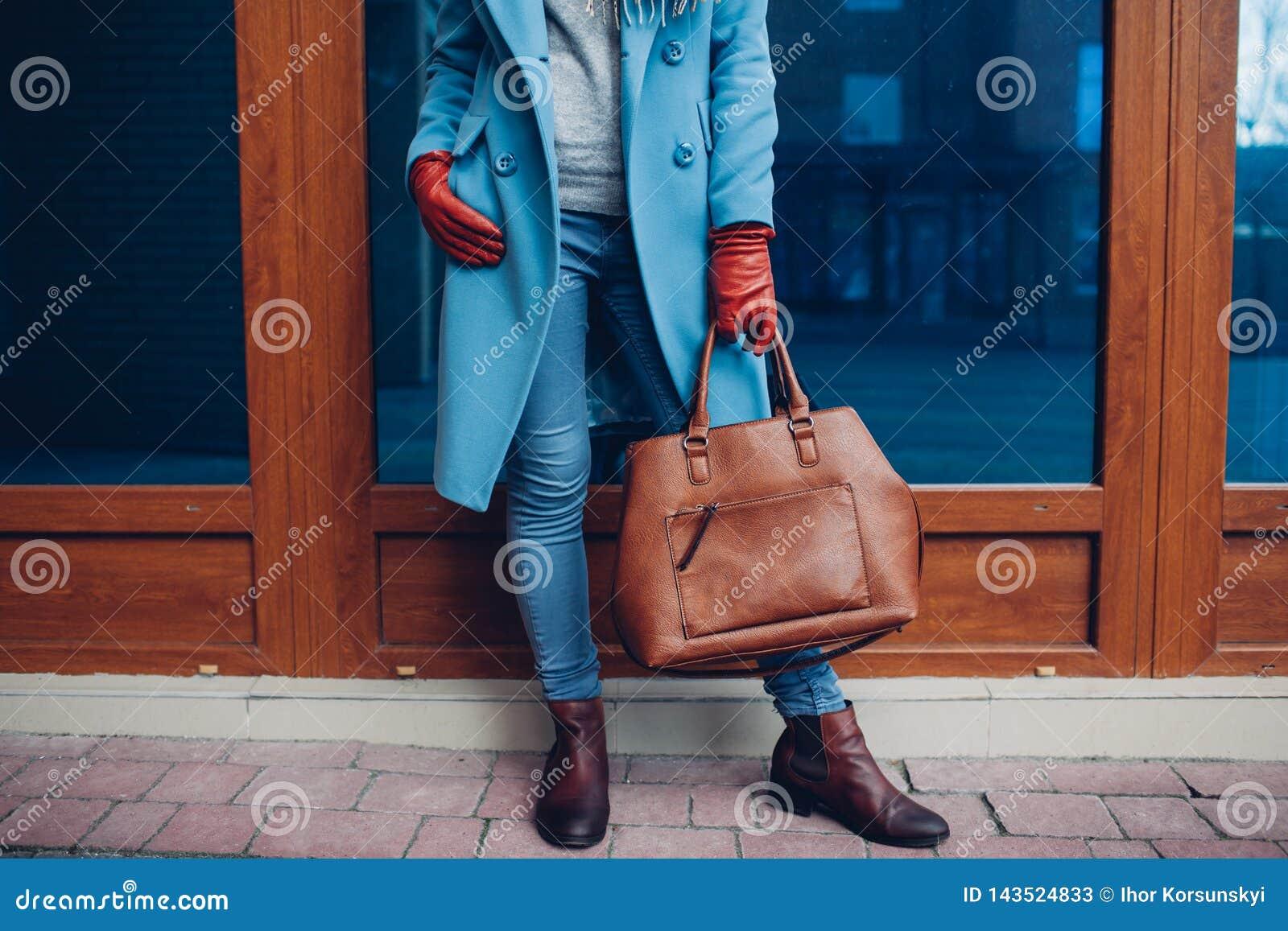 Schoonheid en manier Modieuze modieuze vrouw die laag en handschoenen dragen, die bruine zakhandtas houden