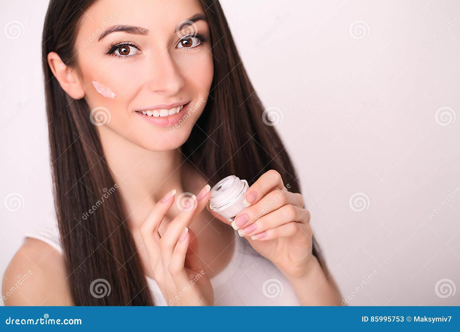 Schoonheid, mensen, schoonheidsmiddelen, skincare en gezondheidsconcept - gelukkige glimlachende jonge vrouw die room toepassen o