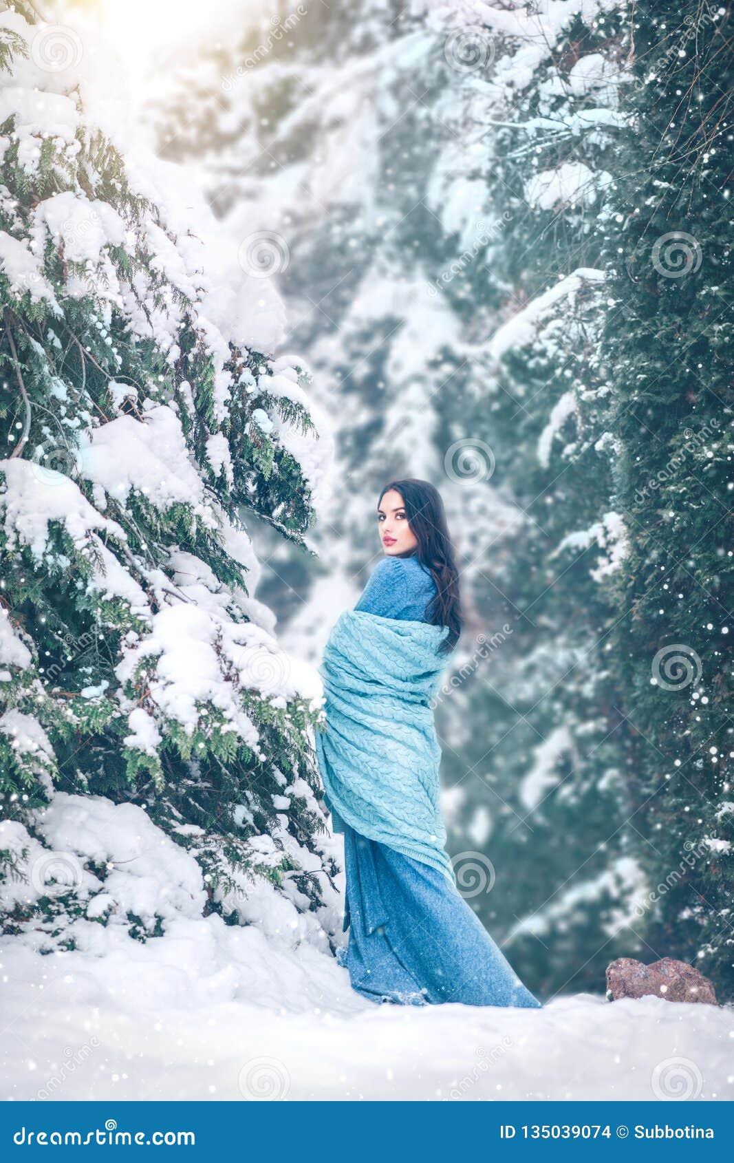 Schoonheids het jonge vrouw behandelde lopen in openlucht in de winterpark onder de spar sneeuw Het mooie modelmeisje stellen