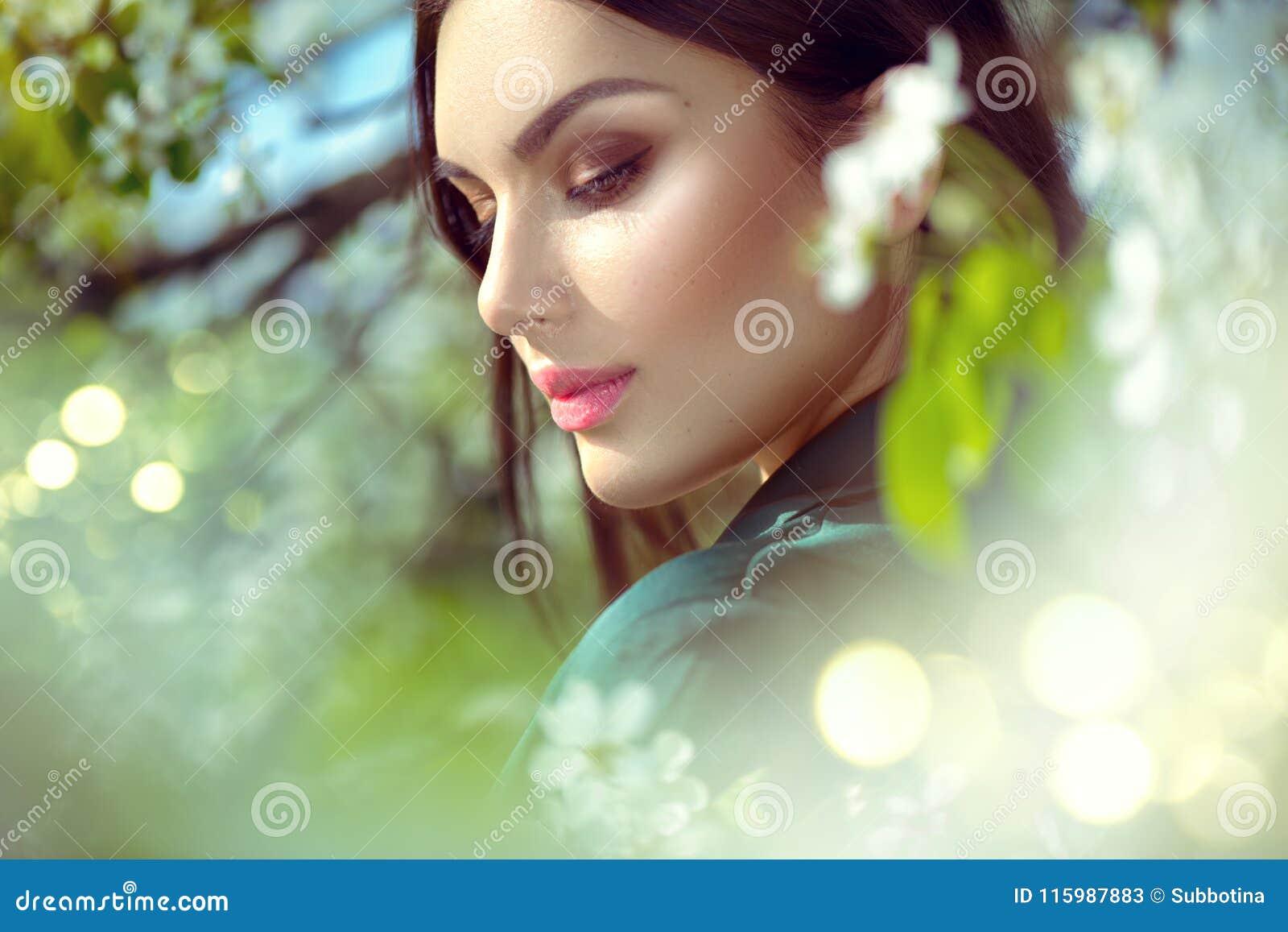 Schoonheids jonge vrouw die van aard in de boomgaard van de de lenteappel, Gelukkig mooi meisje in een tuin met bloeiende fruitbo