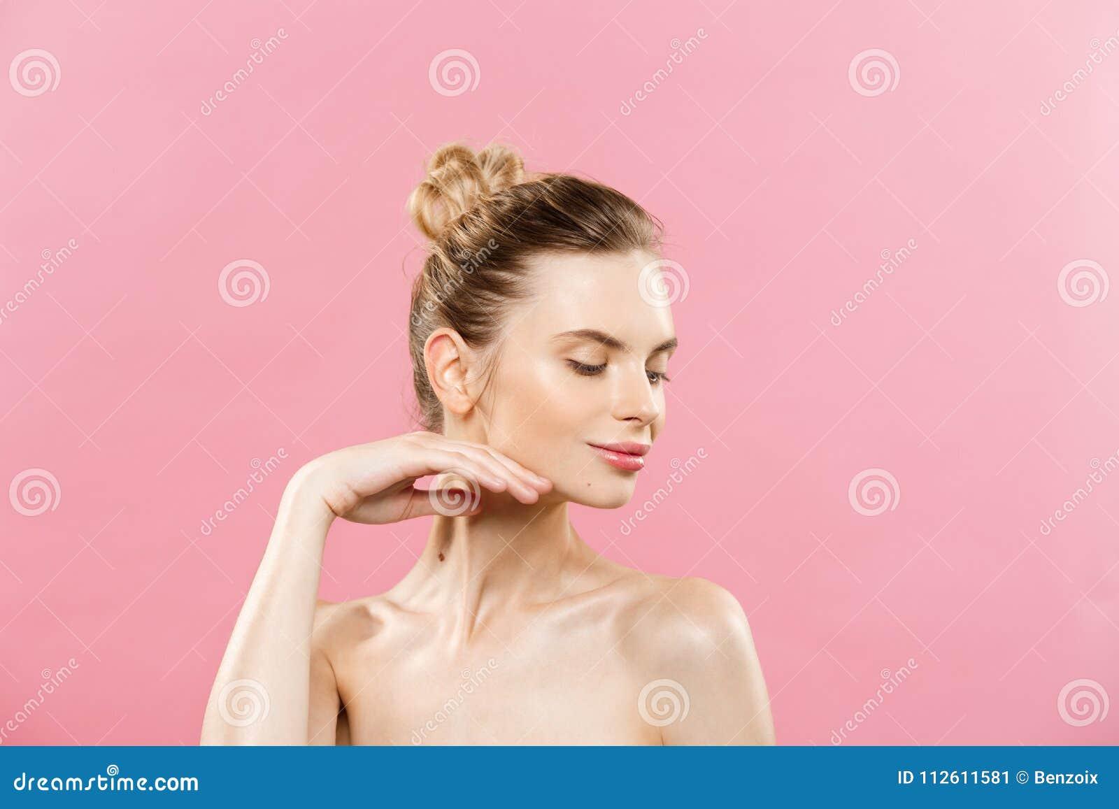 Schoonheidsconcept - Mooie Kaukasische vrouw met schone huid, natuurlijke die samenstelling op heldere roze achtergrond met exemp