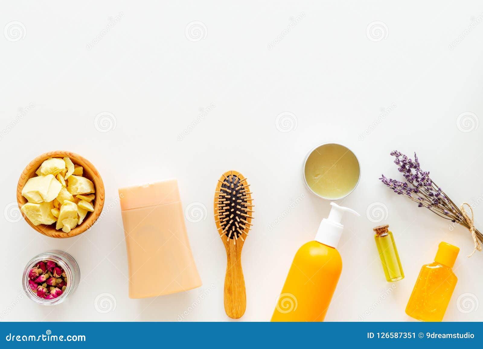 Schoonheidsmiddelen voor haarverzorging met jojoba, argan of kokosnotenolie Flessen en stukken van olie op wit achtergrond hoogst