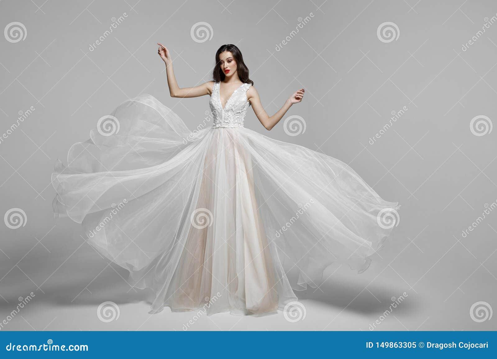 Schoonheidsportret van een jonge vrouw in de lange kleding van de huwelijksmanier in golvende vliegende stof, doek die in wind fl