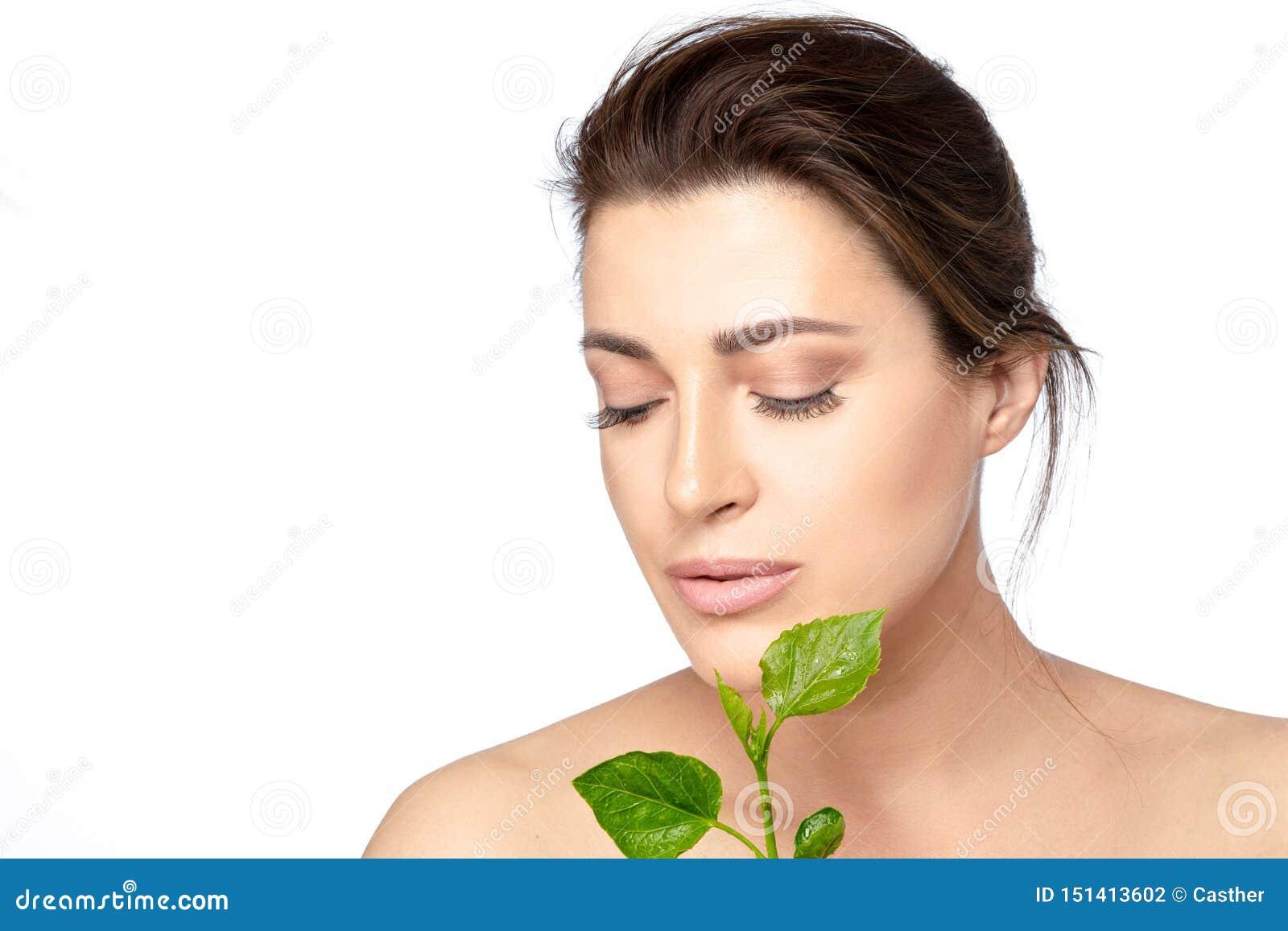Schoonheidsportret van een jonge vrouw met groene bladeren Het natuurlijke skincare, gezondheid en concept van de kuuroordbehande