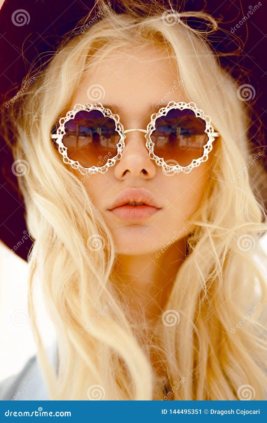 Schoonheidsportret van een sexy blonde met ronde bloemenoogglazen, grote lippen, de golvende haar en hoed van Bourgondië, die cam