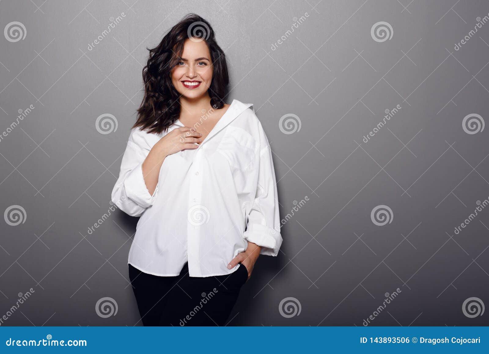 Schoonheidsportret van vrolijke donkerbruine vrouw, slijtage in wit overhemd en zwarte broek, die op een grijze achtergrond wordt