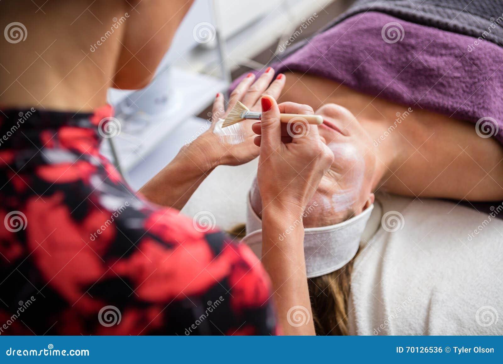 Schoonheidsspecialist Applying Facial Mask op het Gezicht van de Vrouw