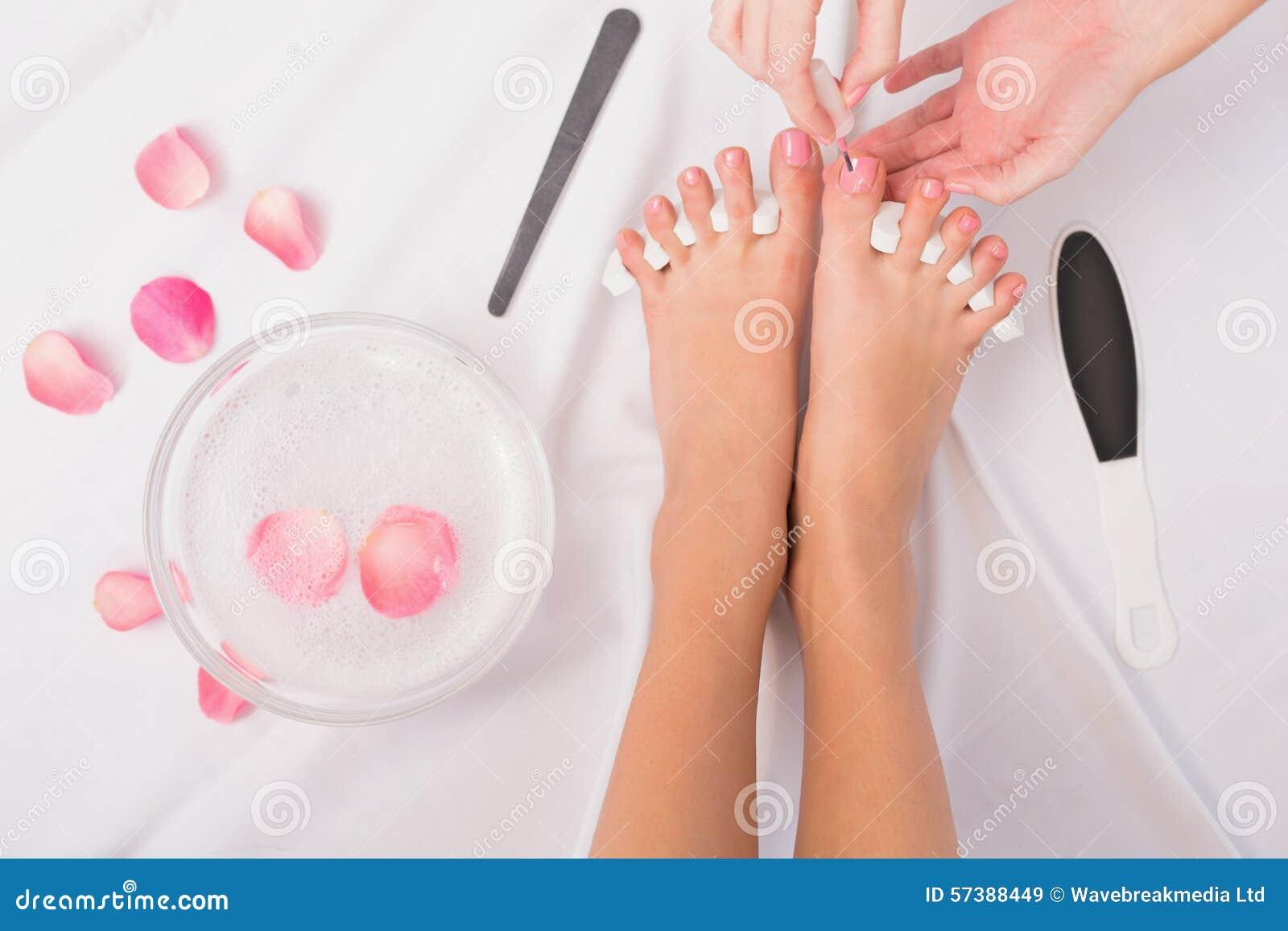 Schoonheidsspecialist het schilderen de teennagels van de vrouw