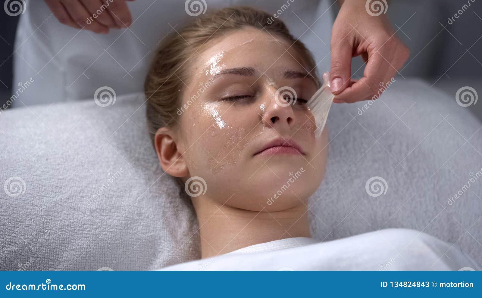 Schoonheidsspecialist het verwijderen blijft van masker van meisjesgezicht, diep het schoonmaken van poriën