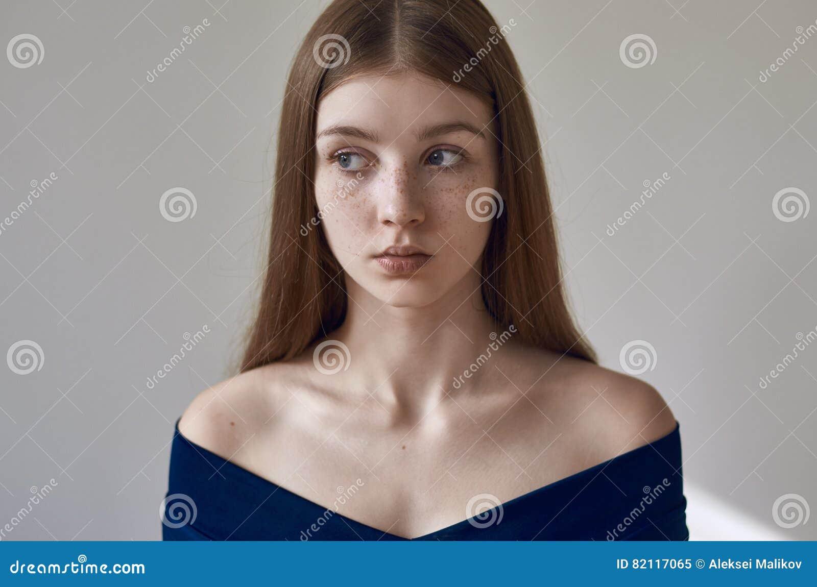 Schoonheidsthema: portret van een mooi jong meisje met sproeten op haar gezicht en het dragen van een blauwe kleding op een witte