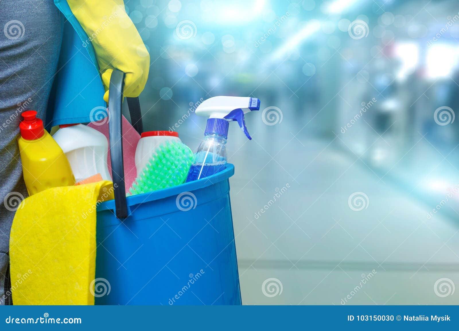 Schoonmaakster met een emmer en schoonmakende producten