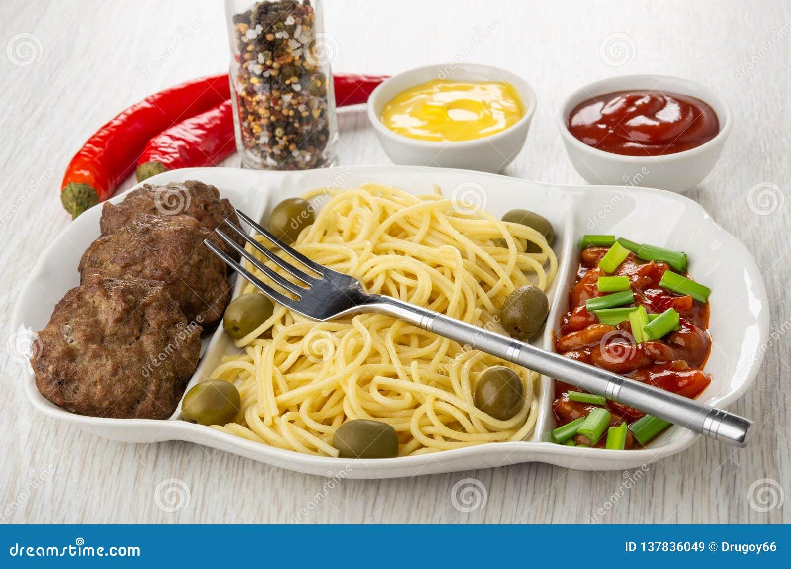 Schotel met spaghetti, kotelet, bonen, ui en olijven, vork, Spaanse peperpeper, specerij, mayonaise en ketchup op lijst