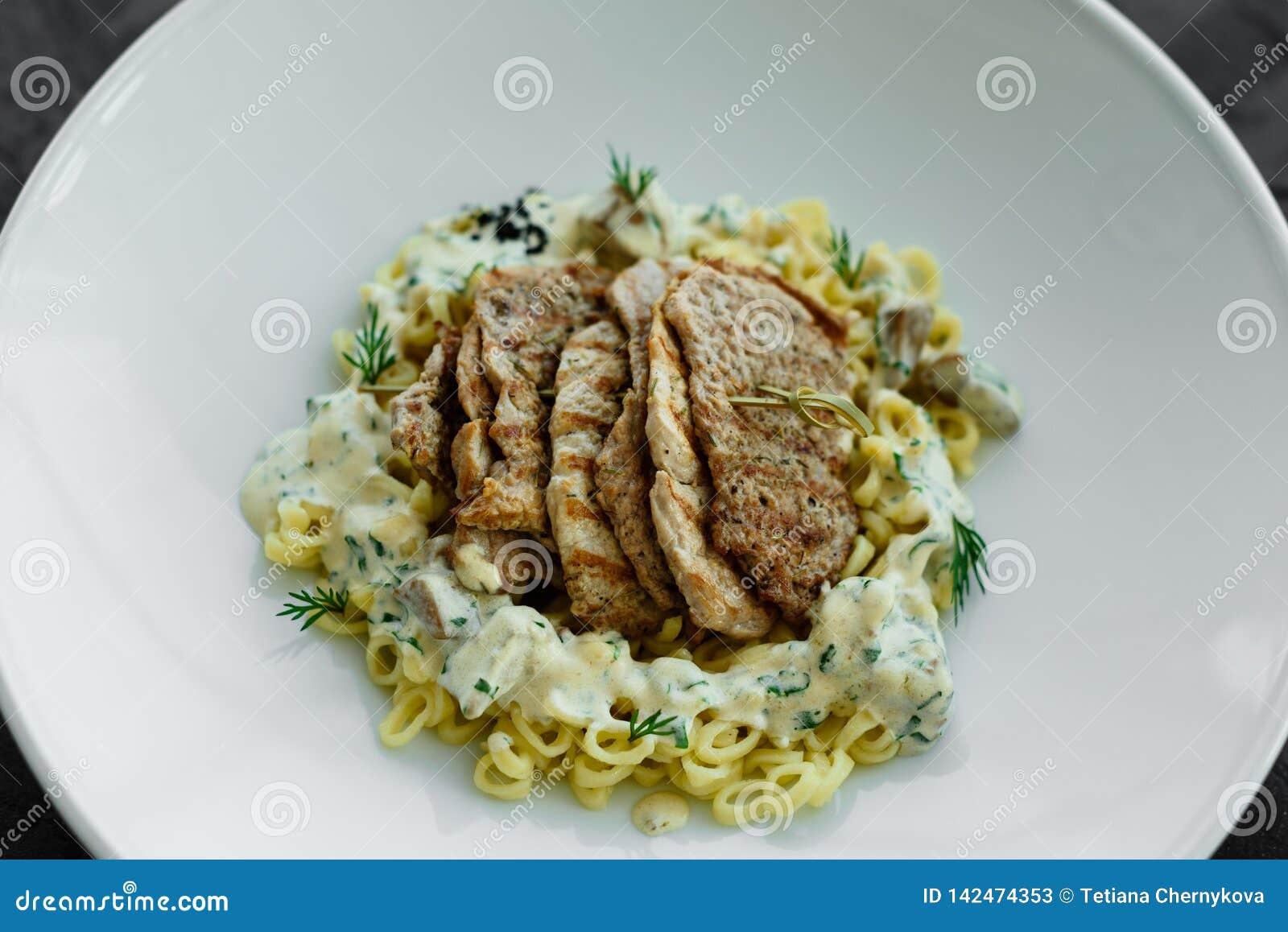 Schotel met vleesstukken, deegwaren, greens en saus van een foiegras