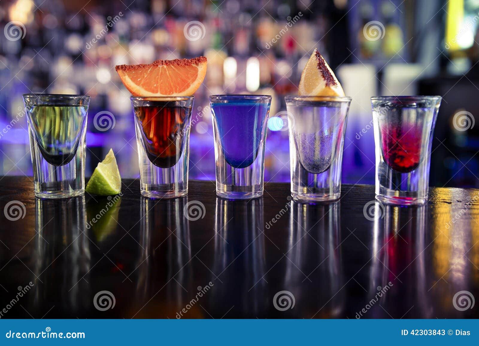 Schoten met alcoholische drank en alcohol in cocktailbar
