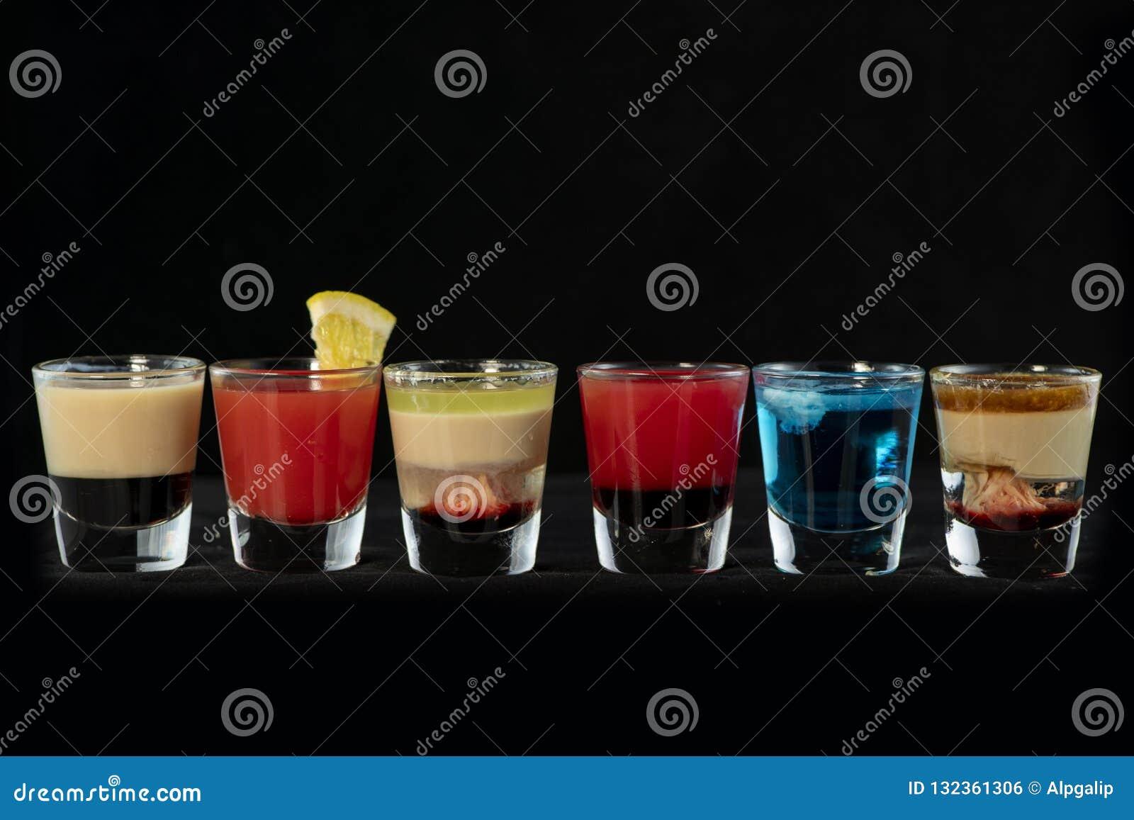 Schoten van de mengelings de alcoholische cocktail samen met geïsoleerde zwarte achtergrond