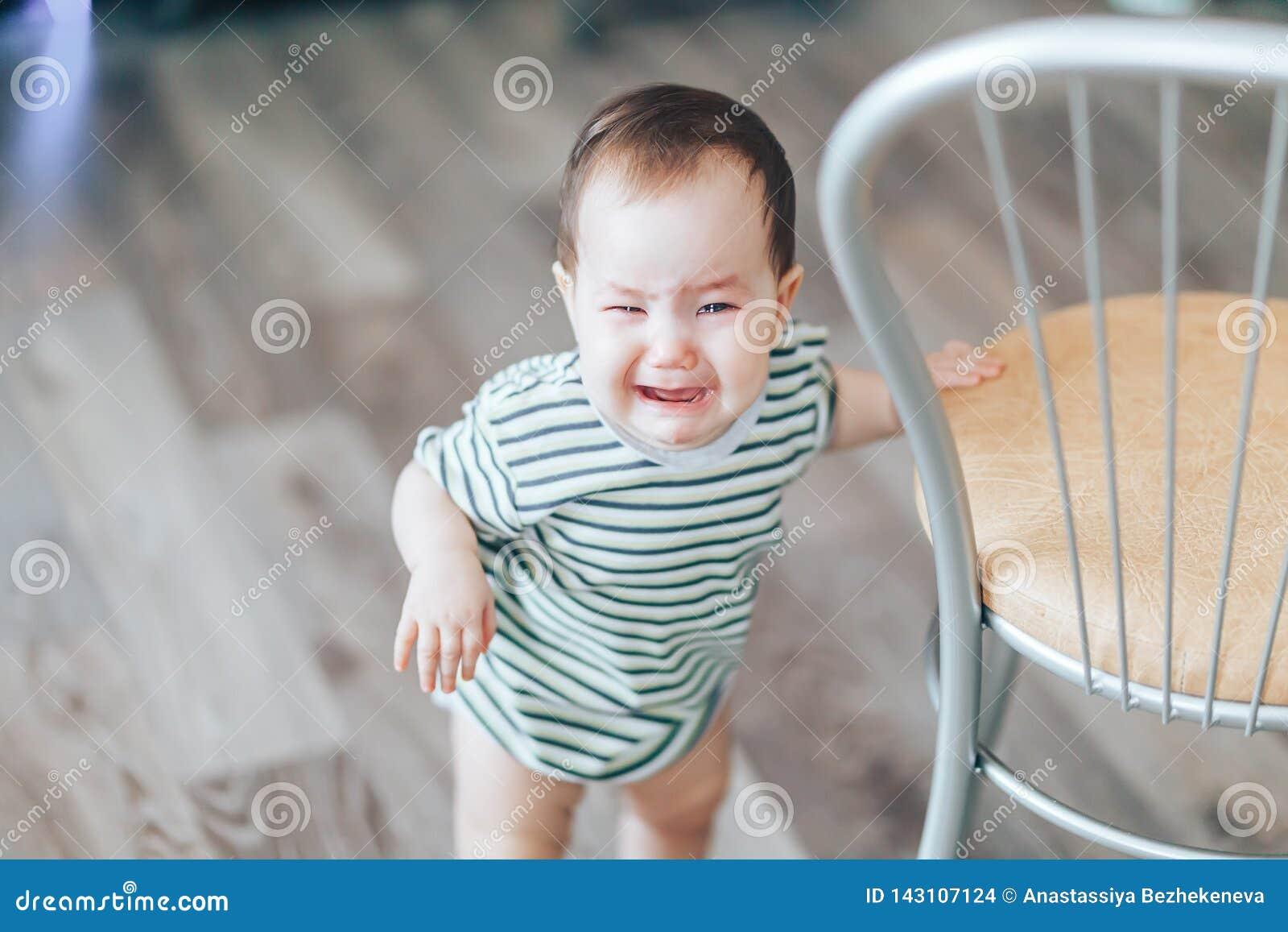 Schreeuwend weinig cutie drk-haired meisje, tribunes die luid schreeuwen die, dichtbij stoel zich thuis bevinden