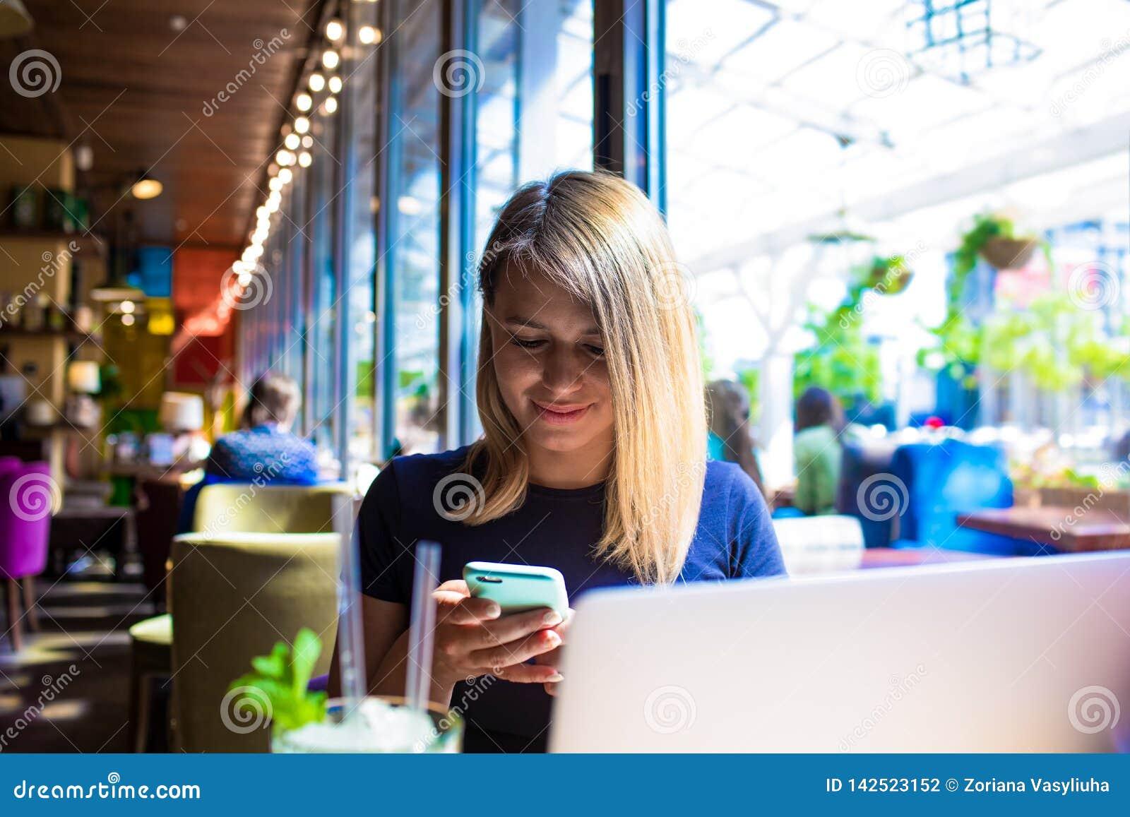Schreibentext des Hippie-Mädchens auf Mobiltelefon nach der Arbeit auf netbook