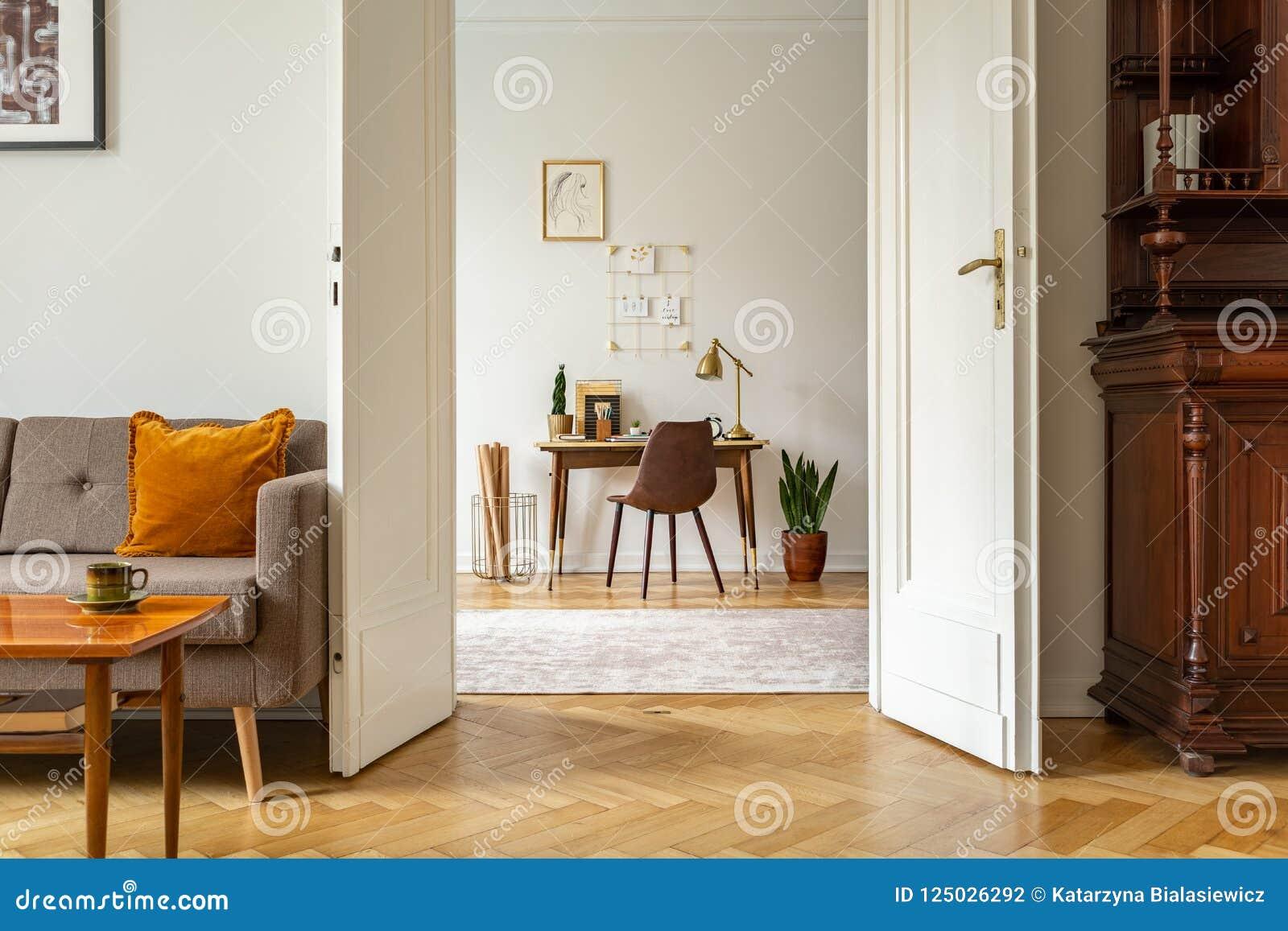 Schreibtisch und Stuhl in einem Innenministeriuminnenraum Ansicht durch Tür eines Weinlesewohnzimmers Reales Foto