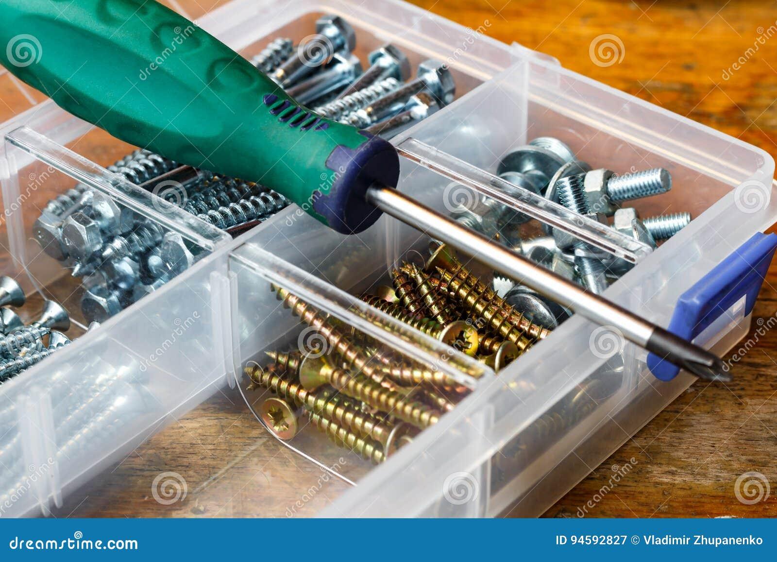 Schroeven en bouten in de opslagdoos met schroevedraaier op de werkbank