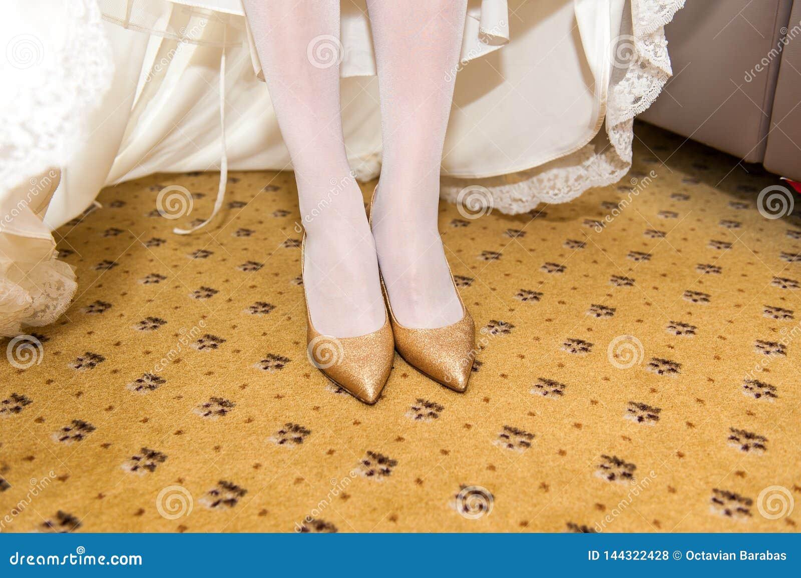 Schuhe der goldenen Heirat auf Brautfüßen