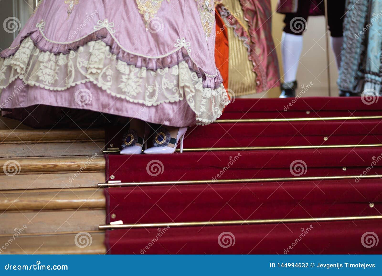 Schuhe - königlicher mittelalterlicher Ball des Retrostils - majestätischer Palast mit den herrlichen Leuten gekleidet in Köni