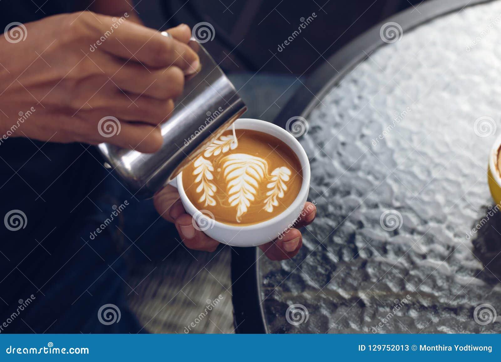 Schuim van de Barista het gietende melk voor het maken van koffie latte kunst met patte
