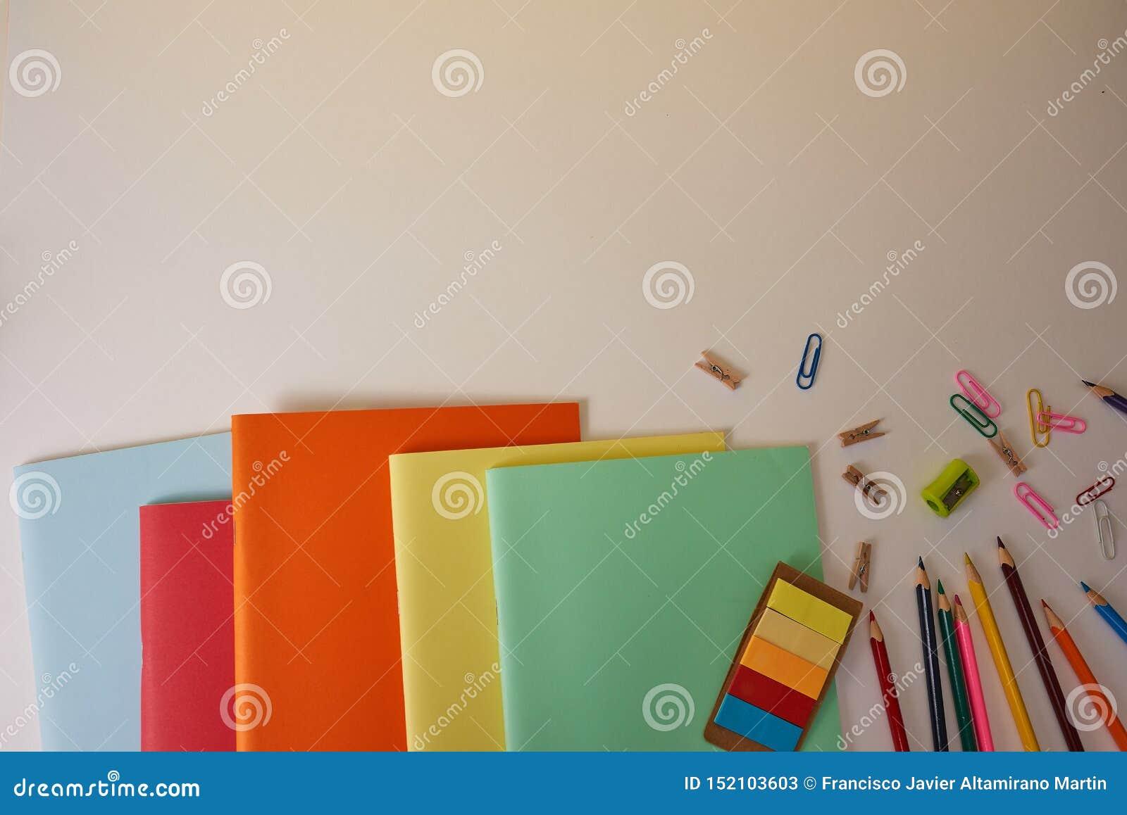 Schulbedarf mit bunten Bleistiften und Notizbüchern