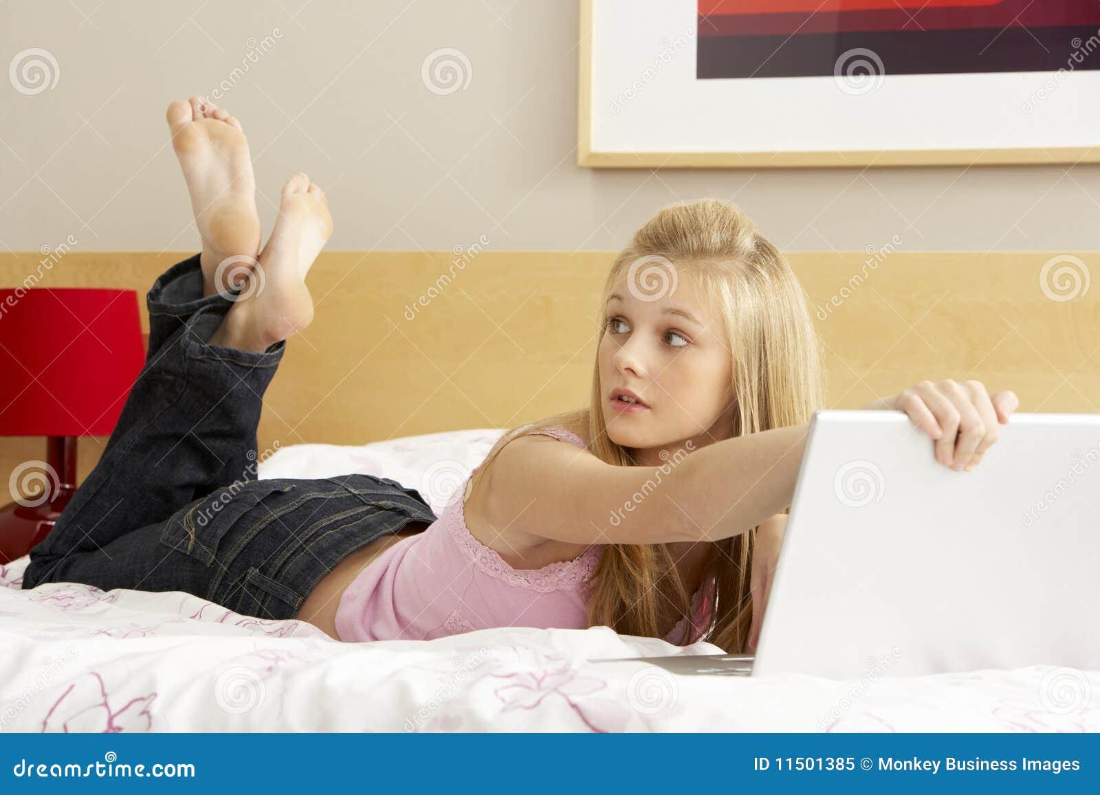 Schuldige tiener die laptop in slaapkamer met behulp van royalty vrije stock foto afbeelding - Foto van tiener slaapkamer ...