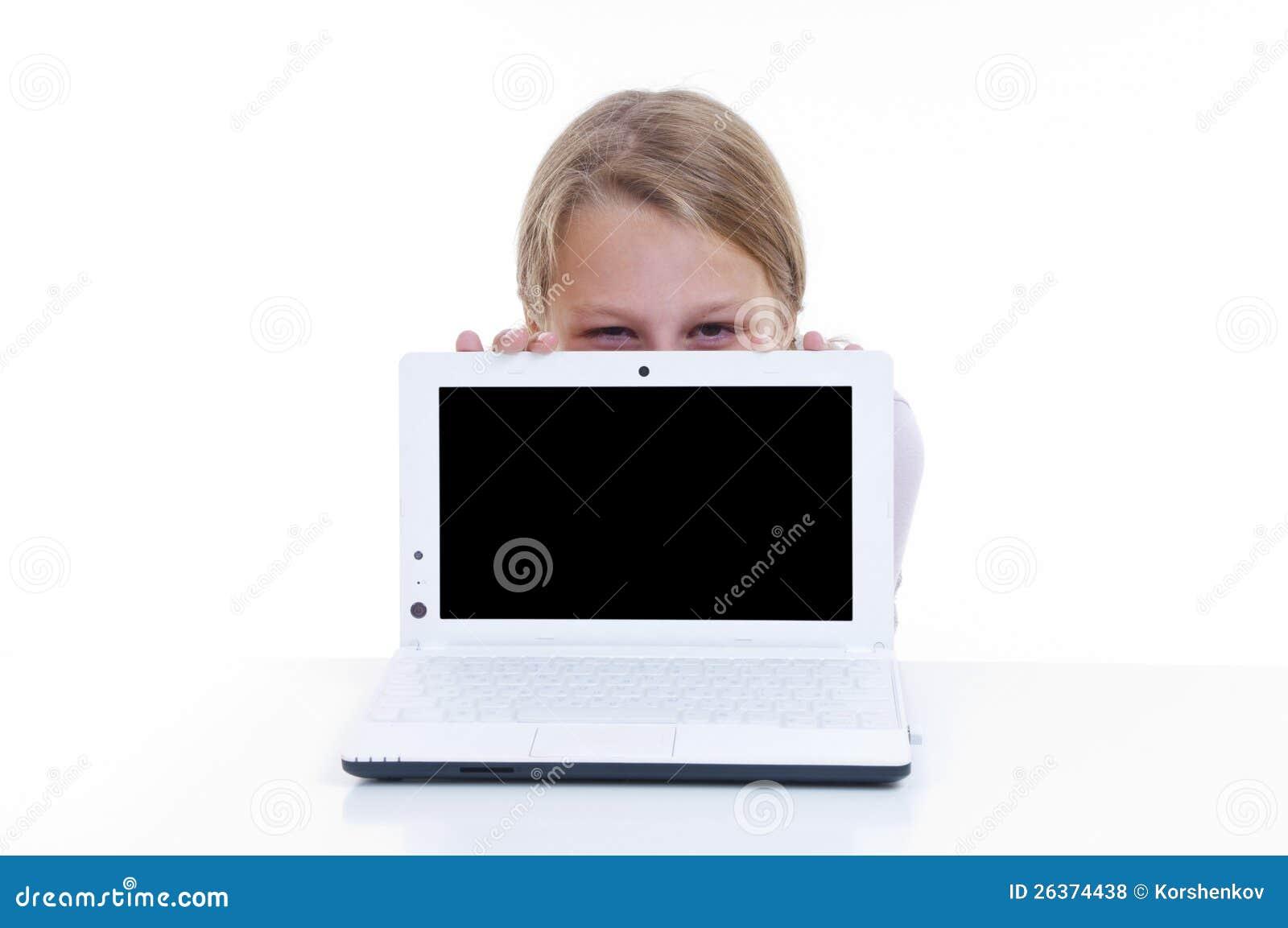 Schulmädchen, das hinter ihrem netbook sich versteckt