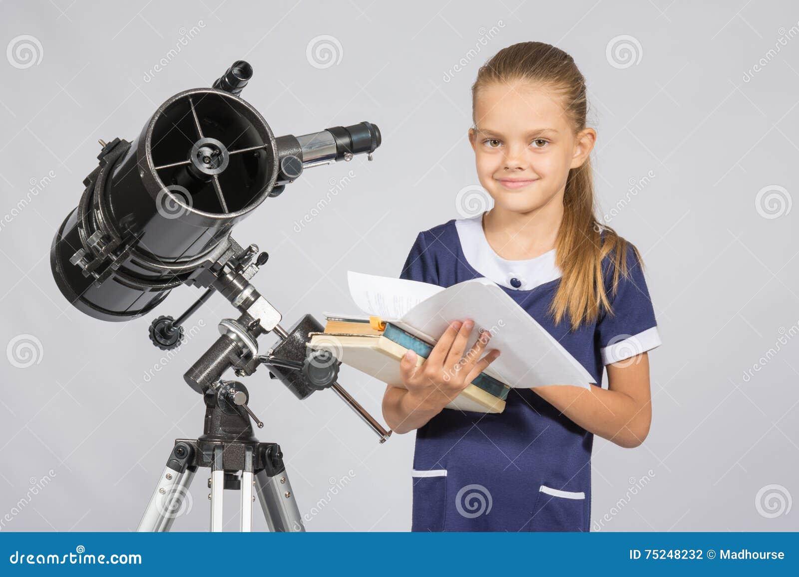 Schulmädchenastronom der durch die bücher stehen am teleskop