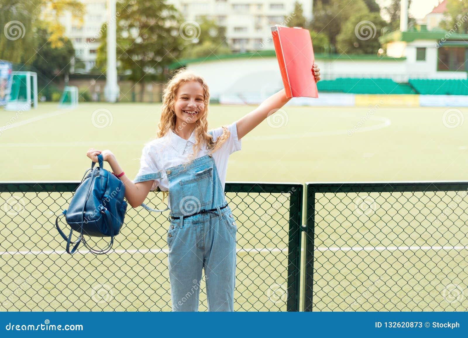 Schulmädchenblondine mit den blauen Augen, die einen roten Ordner und einen Rucksack halten