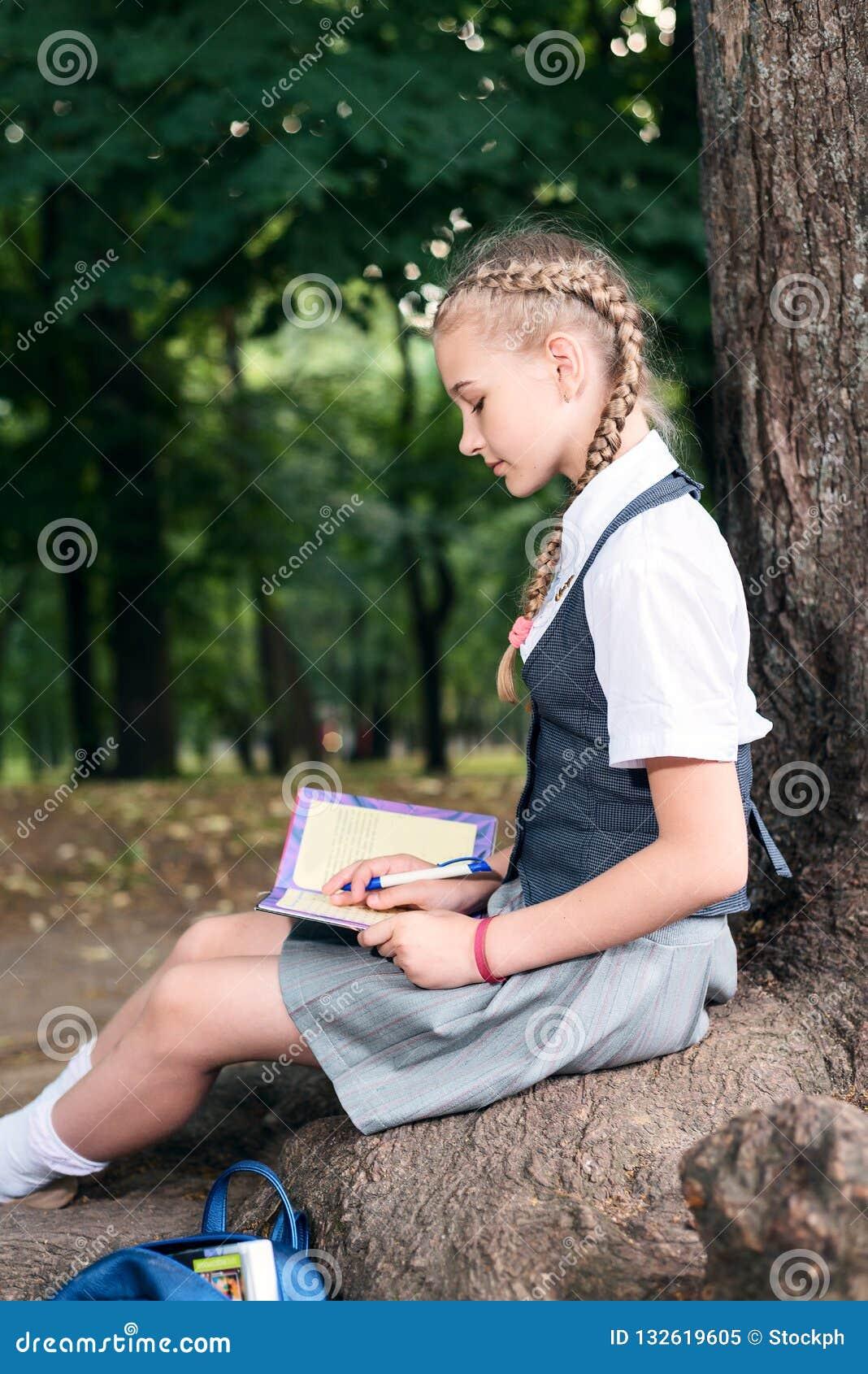 Schulmädchenjugendlicher, der ein Buch in einem Park nahe einem Baum liest