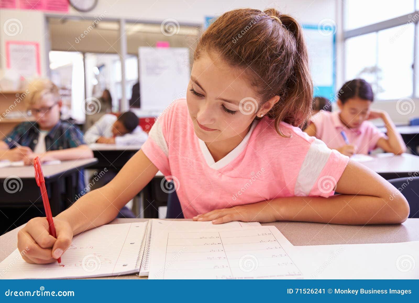 Schulmädchenschreiben an ihrem Schreibtisch in einer grundlegenden Schulklasse